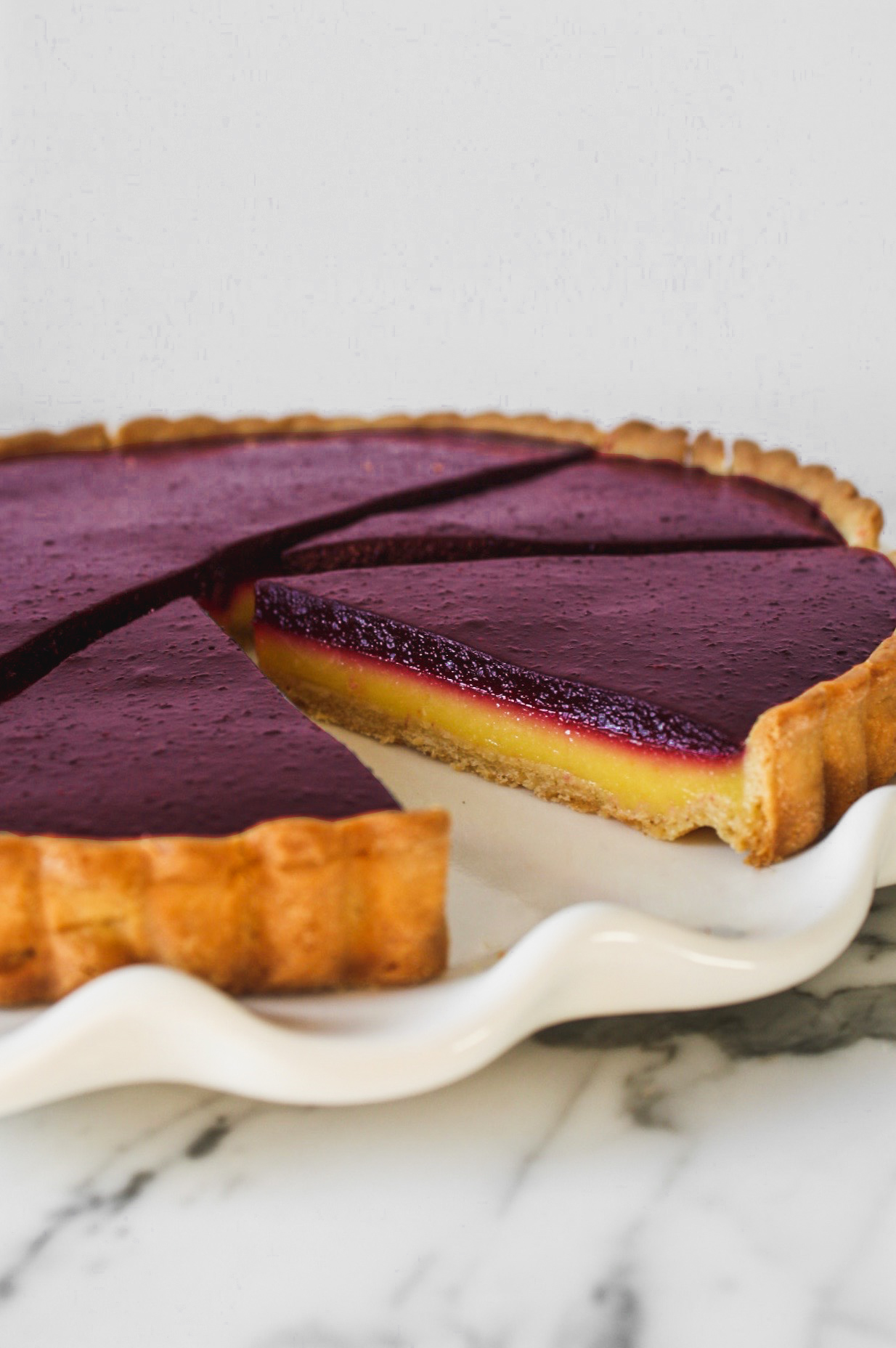 Blueberry lemon tart with yellow and purple layers, set on a gray plate on top of a marble surface.