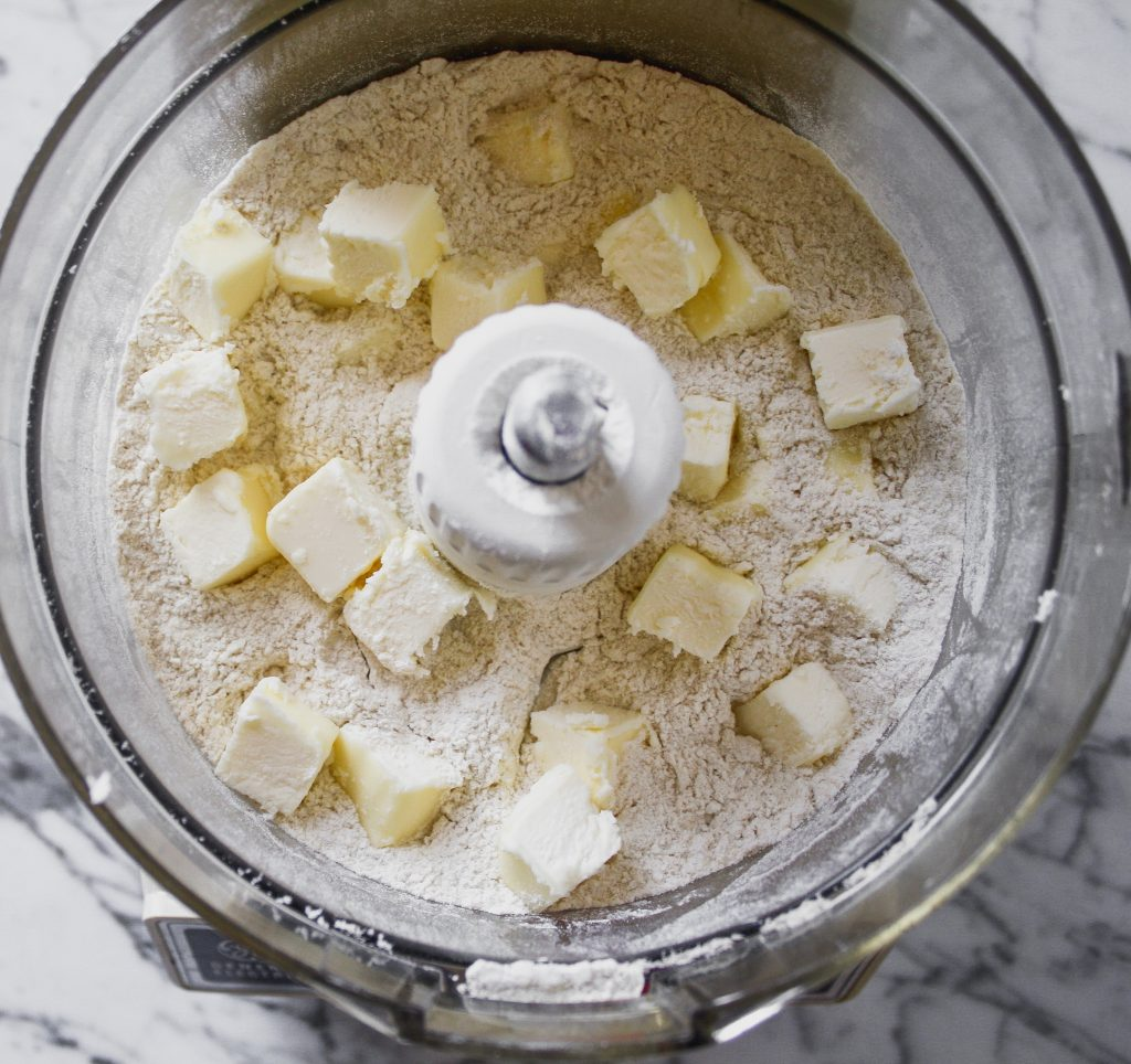 Butter cubes on top of flour in a food processor.