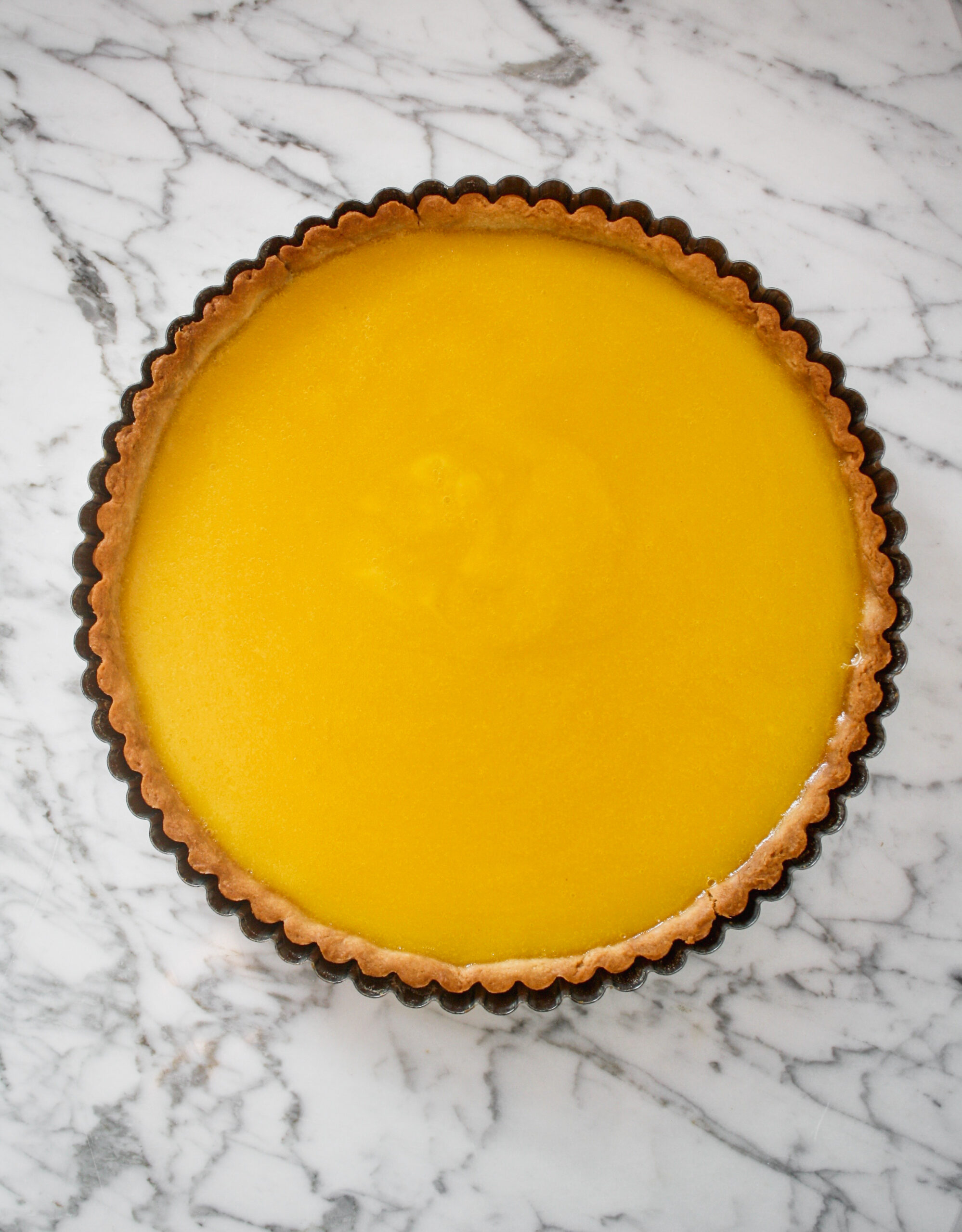 Tart pan lined with baked tart crust and filled with lemon curd set on top of a marble surface.