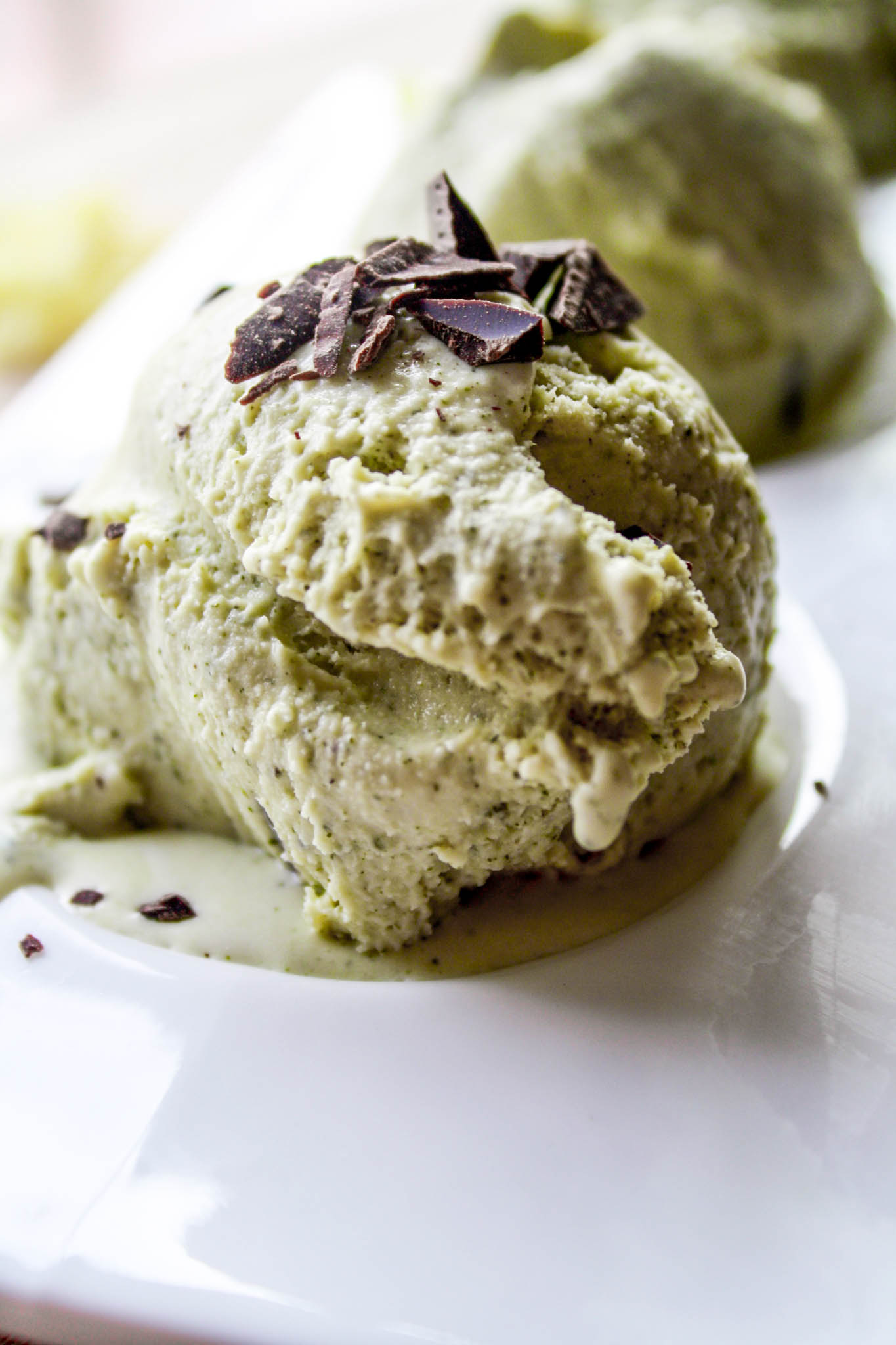 Photograph of a scoop of green tea ice cream on a white plate.