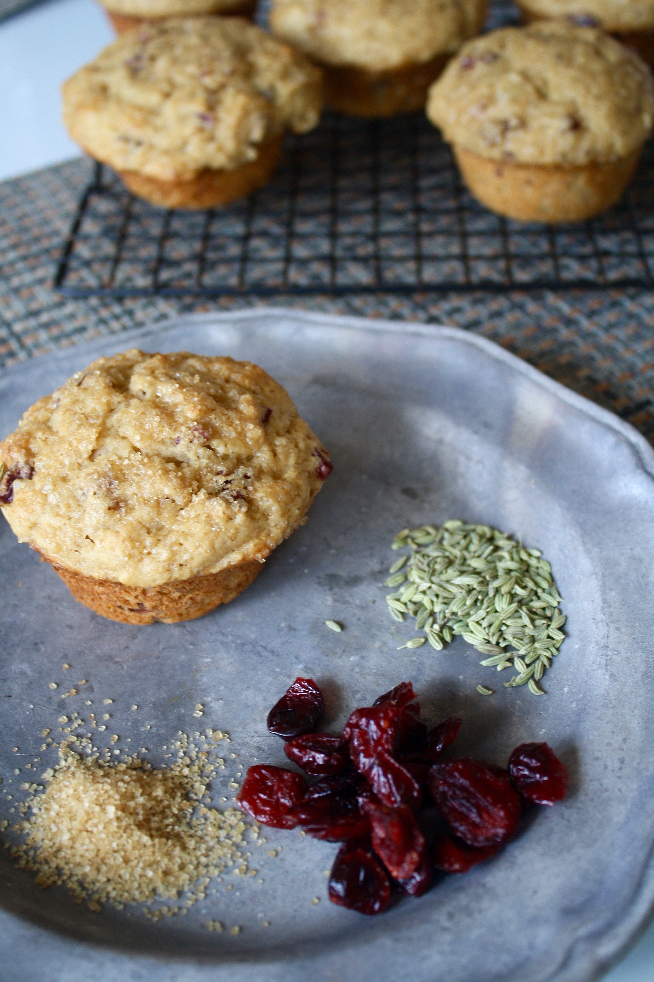 Photograph of pear muffins on a wire baking sheet set on a white table with a metal plate
