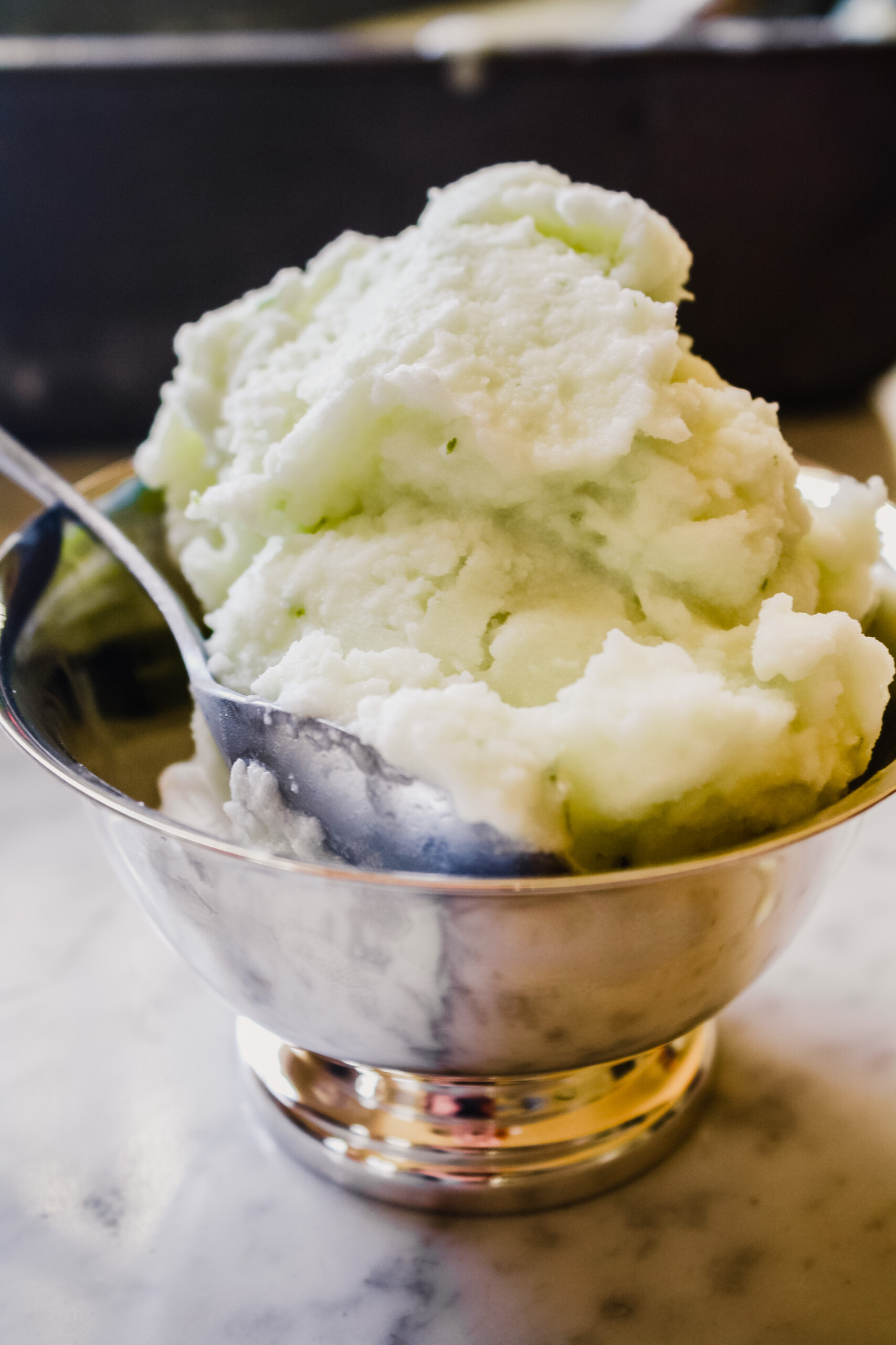 Photograph of sorbet piled high in a silver bowl.