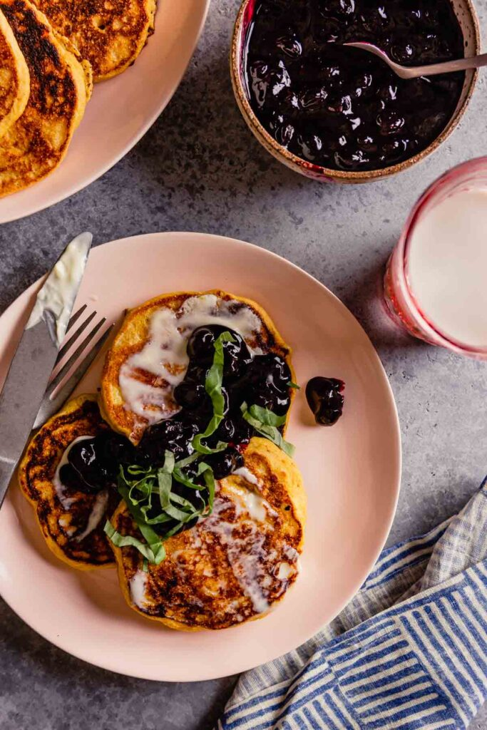 yellow pancakes on a pink plate topped with blueberry sauce and fresh basil
