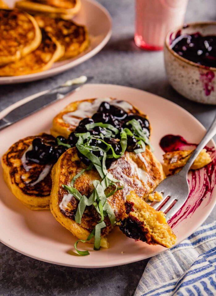 pancakes on a pink plate with a bite on a fork with blueberry compote on top