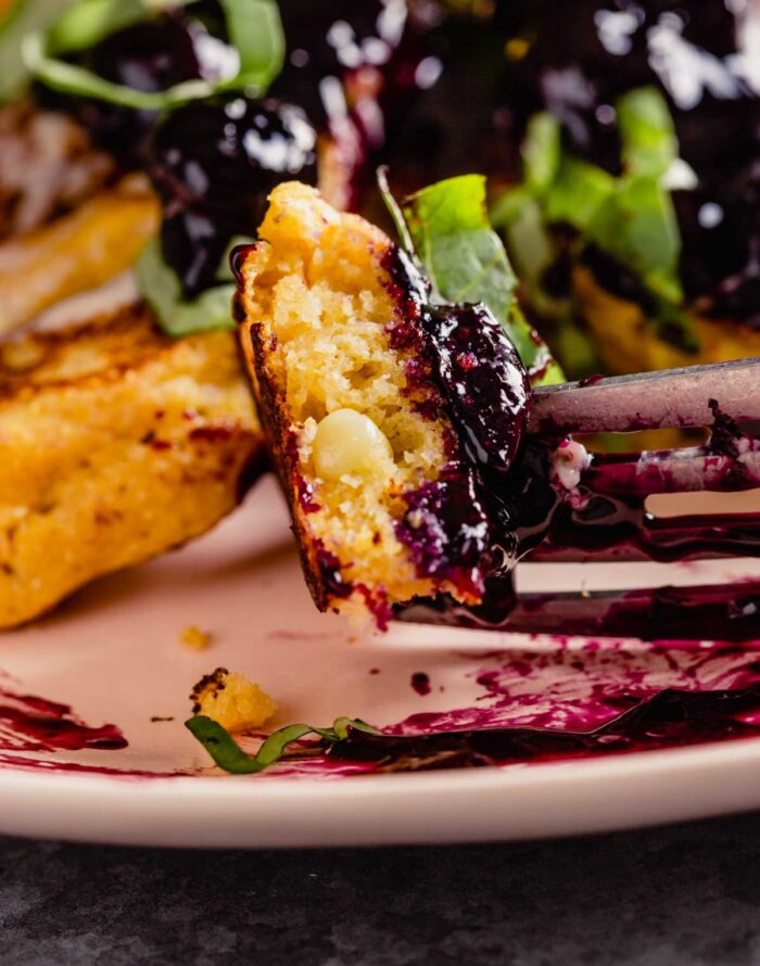 a bite of cornmeal pancakes on a fork with blueberry compote on top