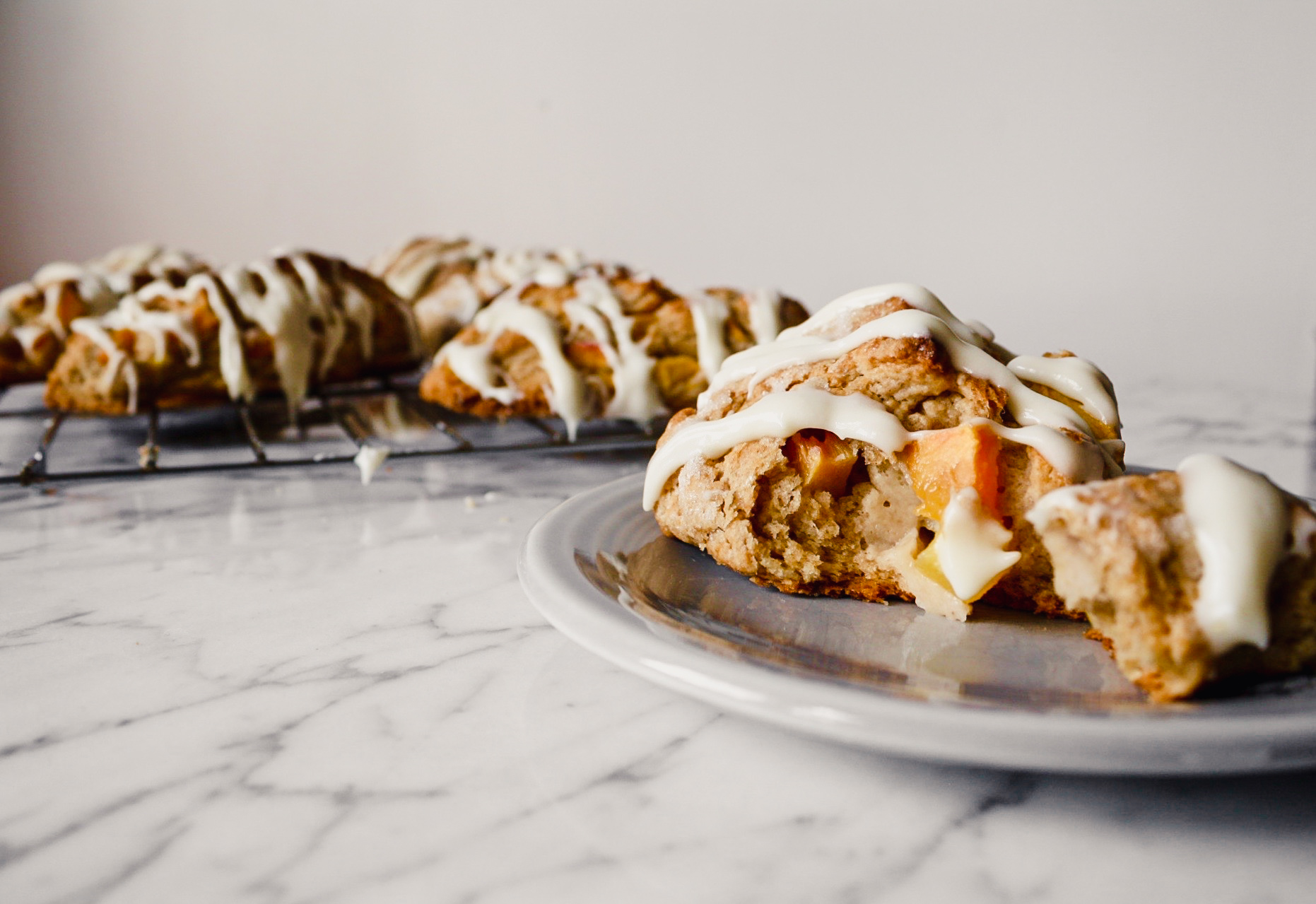 Peach scones with a cream cheese drizzle set on a wire rack