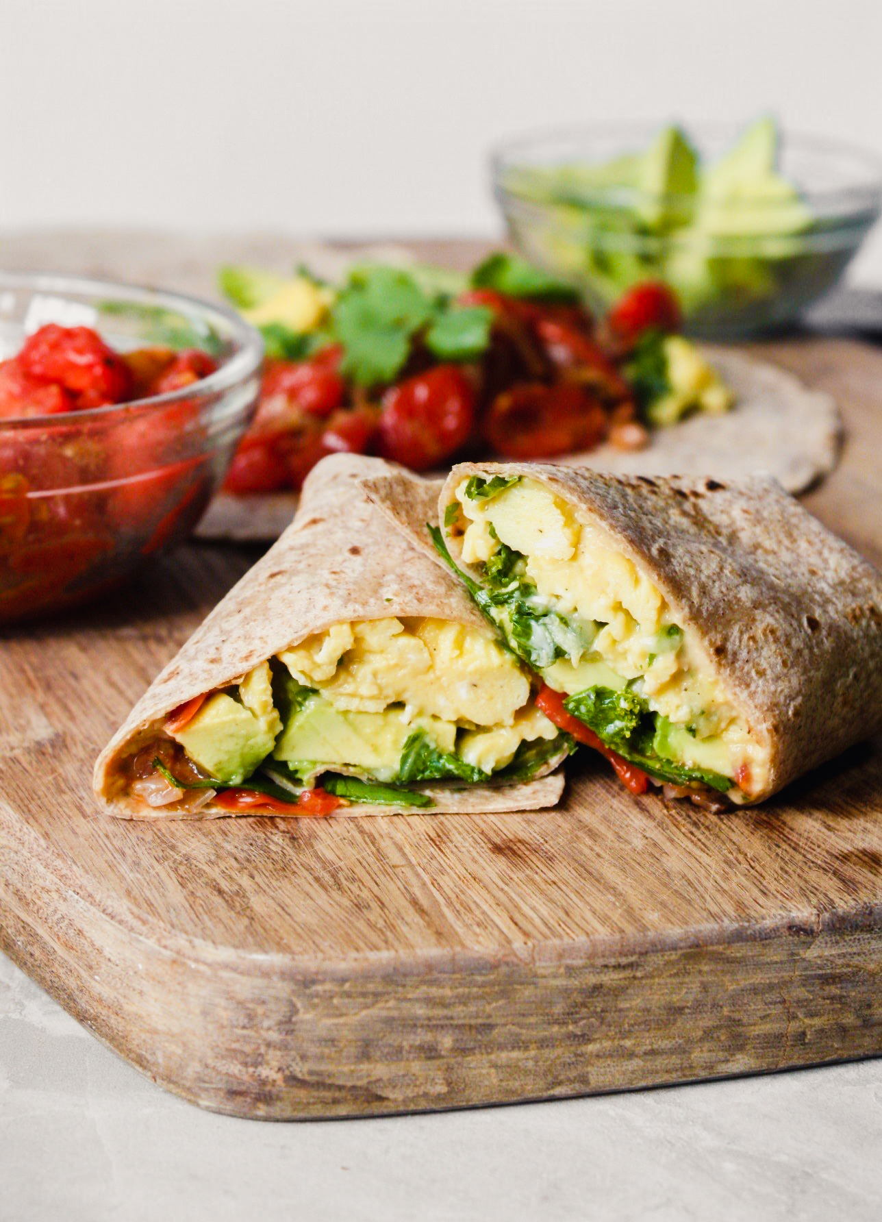 Photograph of a breakfast burrito on a wood cutting board