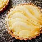 Overhead image of a mini tart on a balking sheet topped with layered of poaches pears