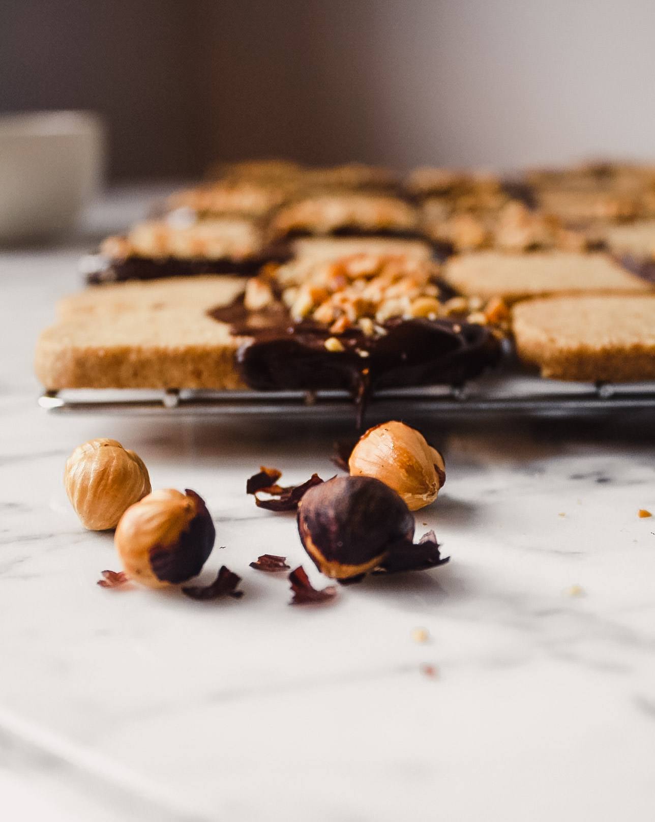 Photograph of toasted hazelnuts laying on a white marble table