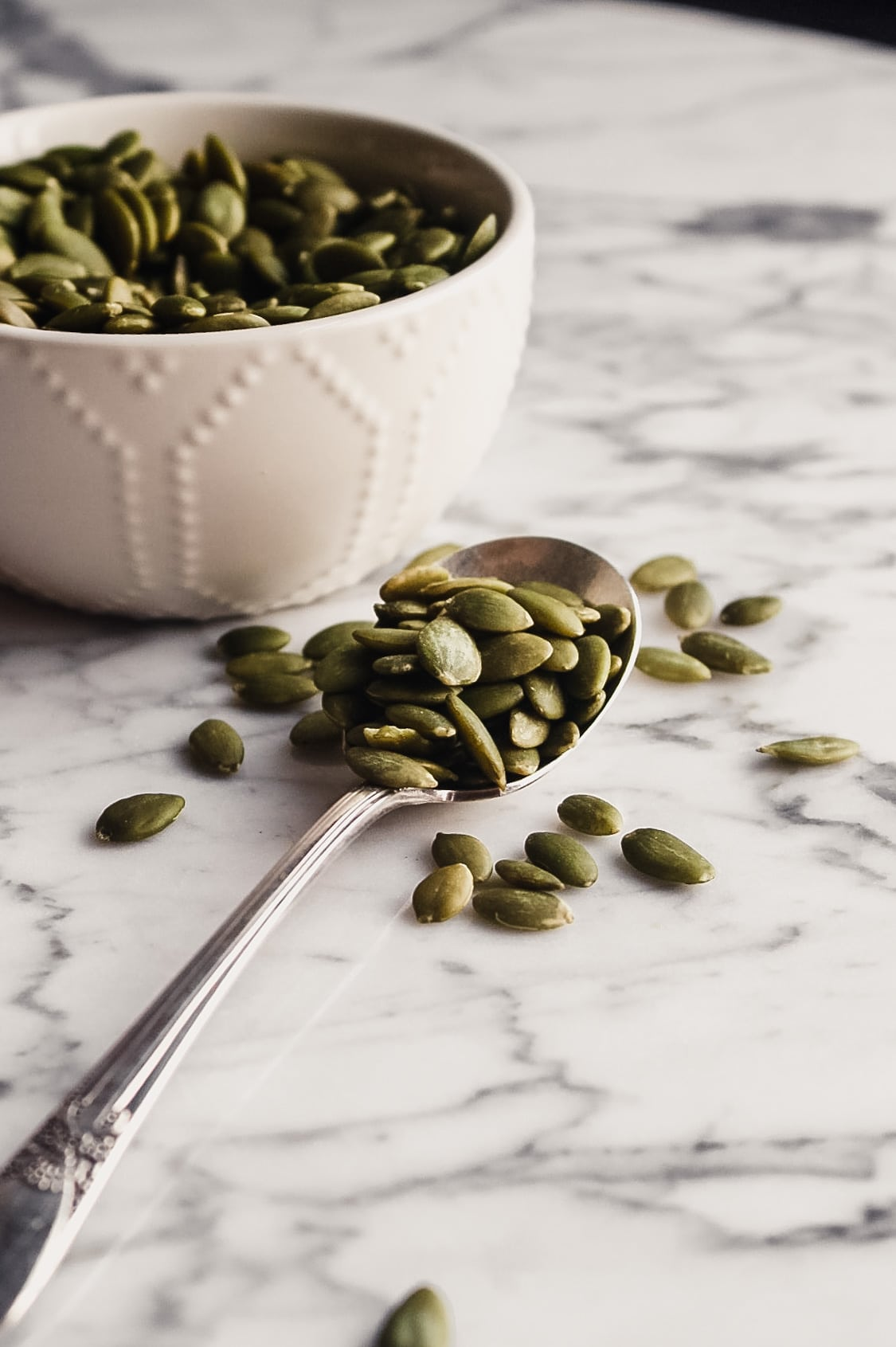 Photograph of pumpkin seeds in a white bowl and scooped into a spoon