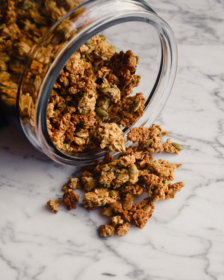 Photograph of granola spilling out of a large glass jar into a marble table