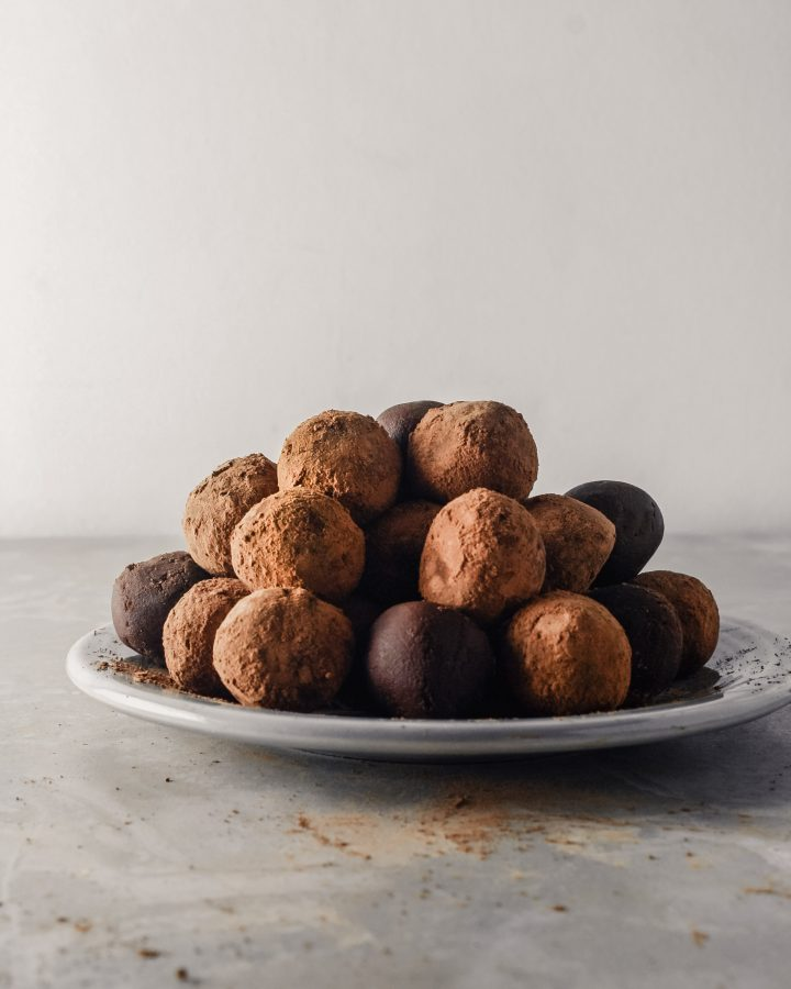 Photograph of dark chocolate truffles stacked on top of a gray plate