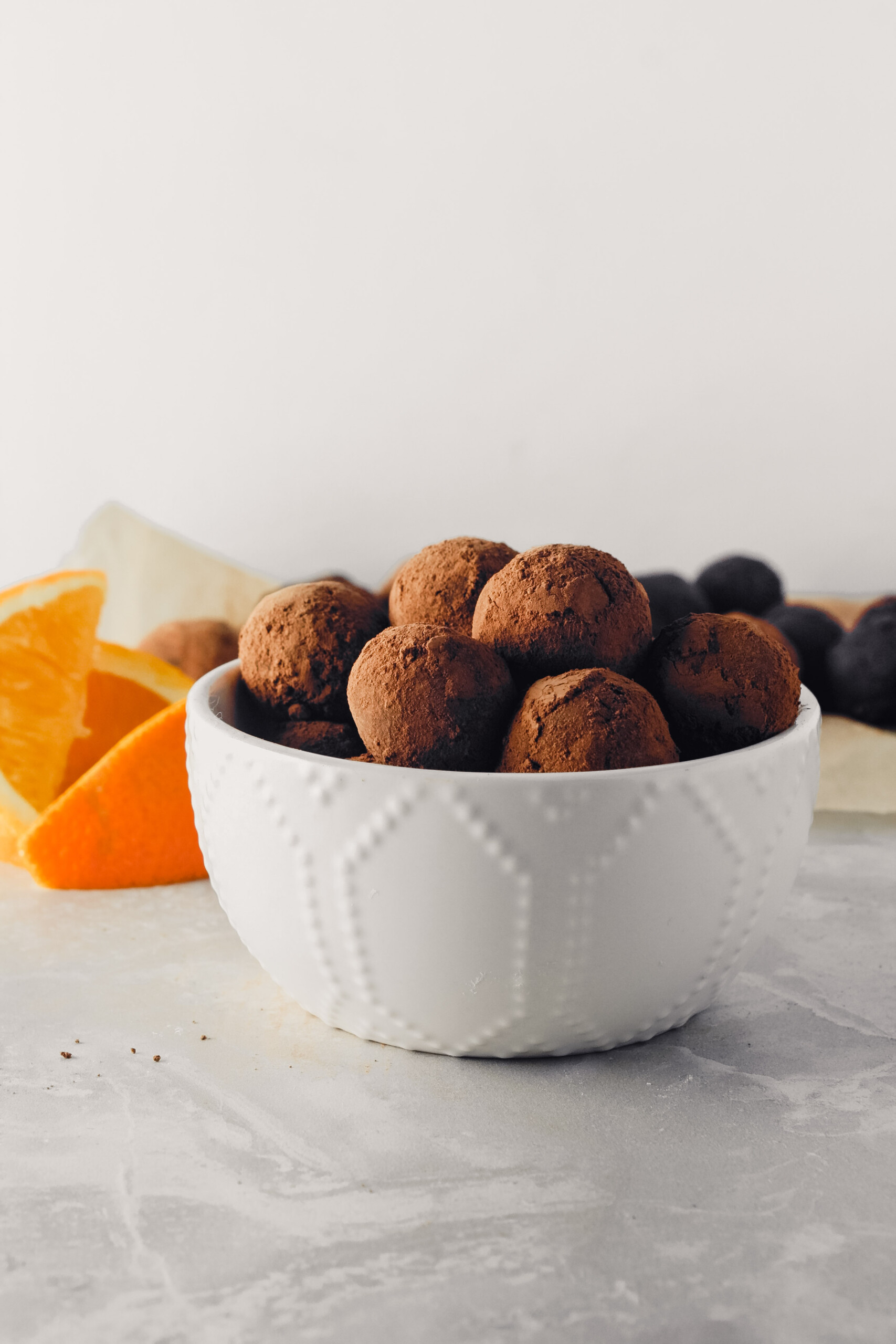 Photograph of vegan dark chocolate truffles stacked in a white bowl, one with a bite taken out of it.