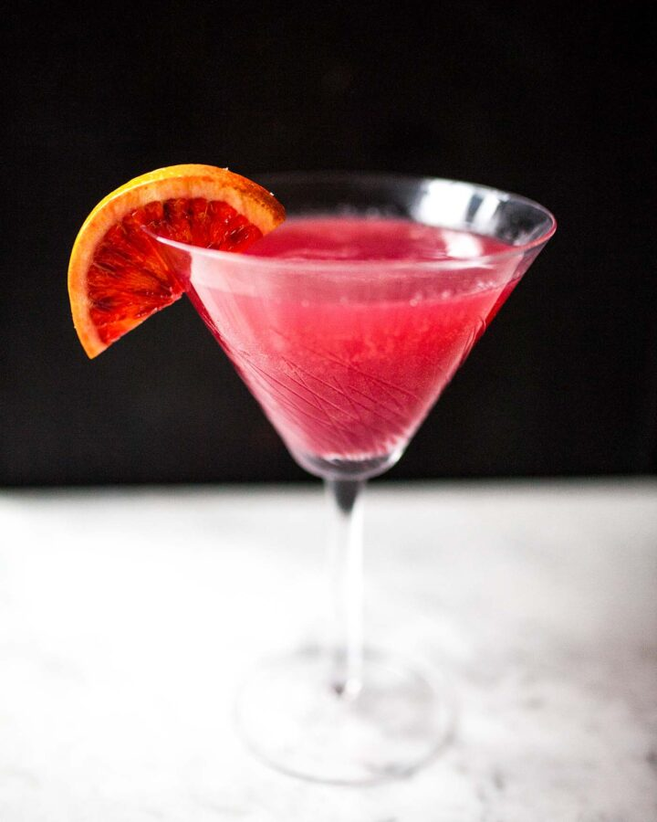 Photograph of a pink cocktail in a martini glass set on a marble table