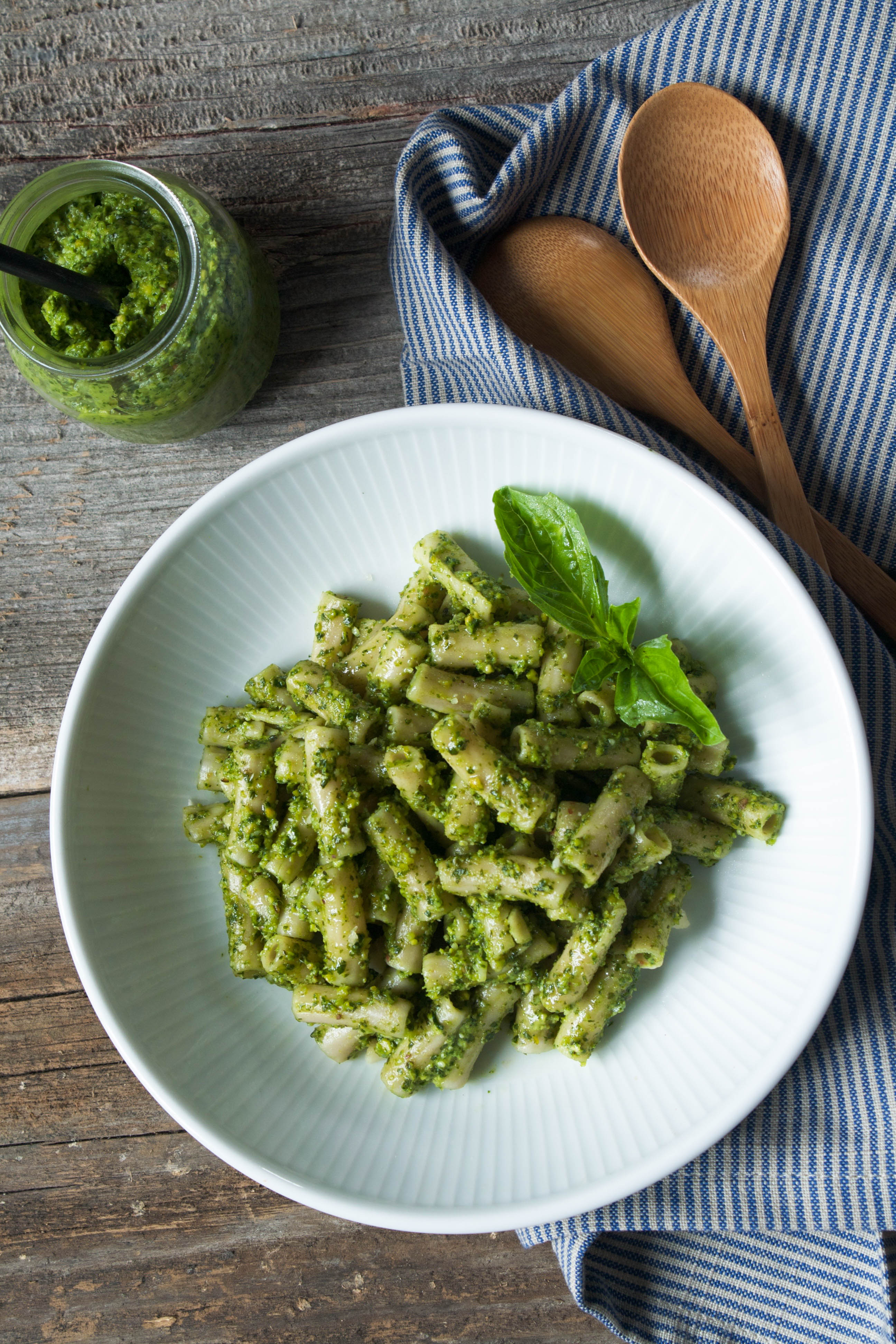Photo of pesto pasta in a white bowl on a wood table