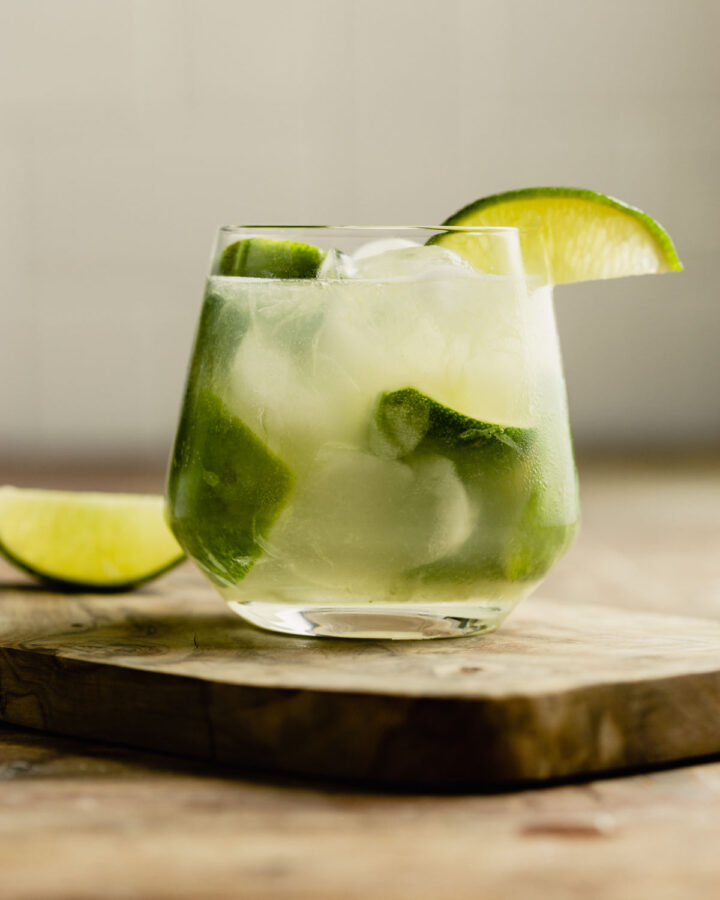 caipirinha cocktail in a rocks glass set on a wood table