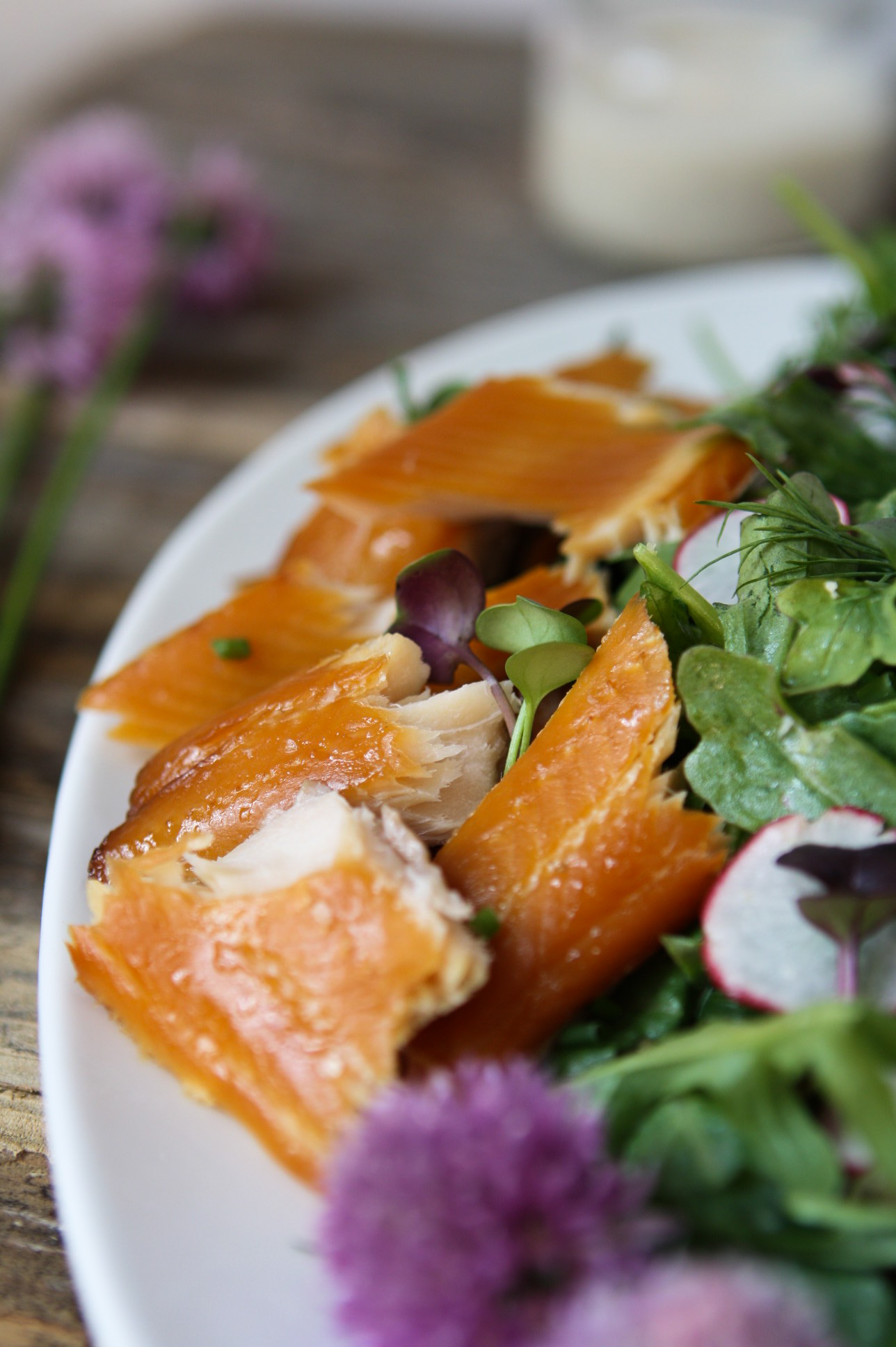 Close up photo of smoked trout on top of spring greens on a white plate.