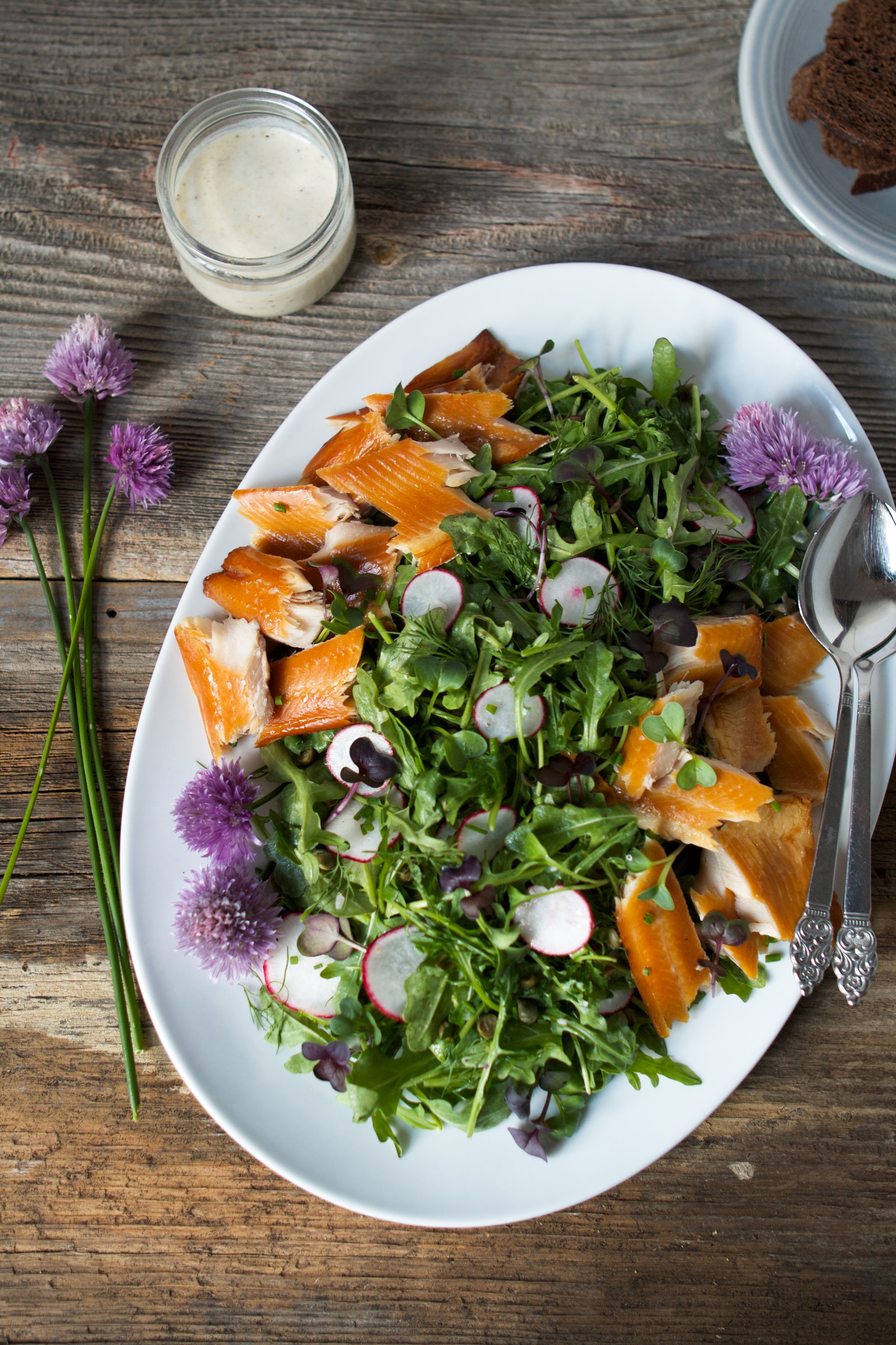 Spring green salad with smoked trout on a large white plate set on a worn wood background.