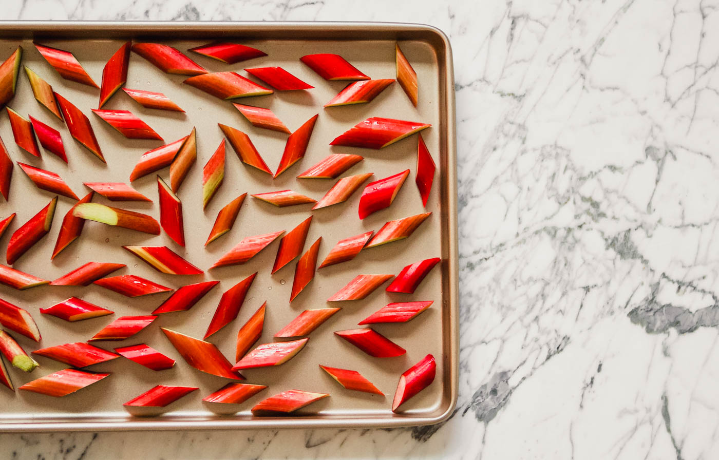 Photograph of rhubarb pieces scattered on a sheet pan.