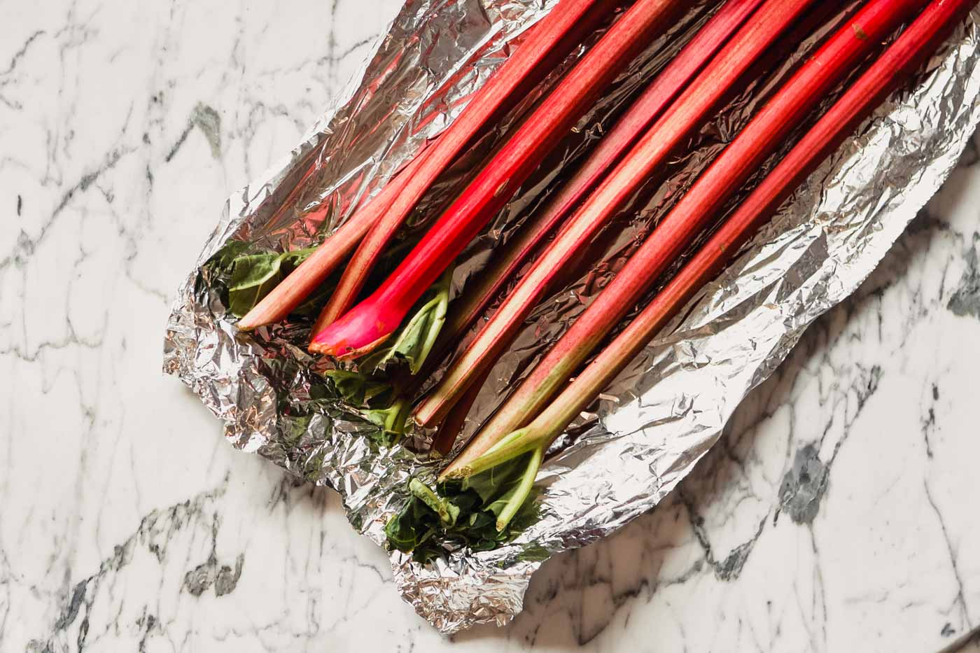 Photograph of stalks of rhubarb set in a piece of foil