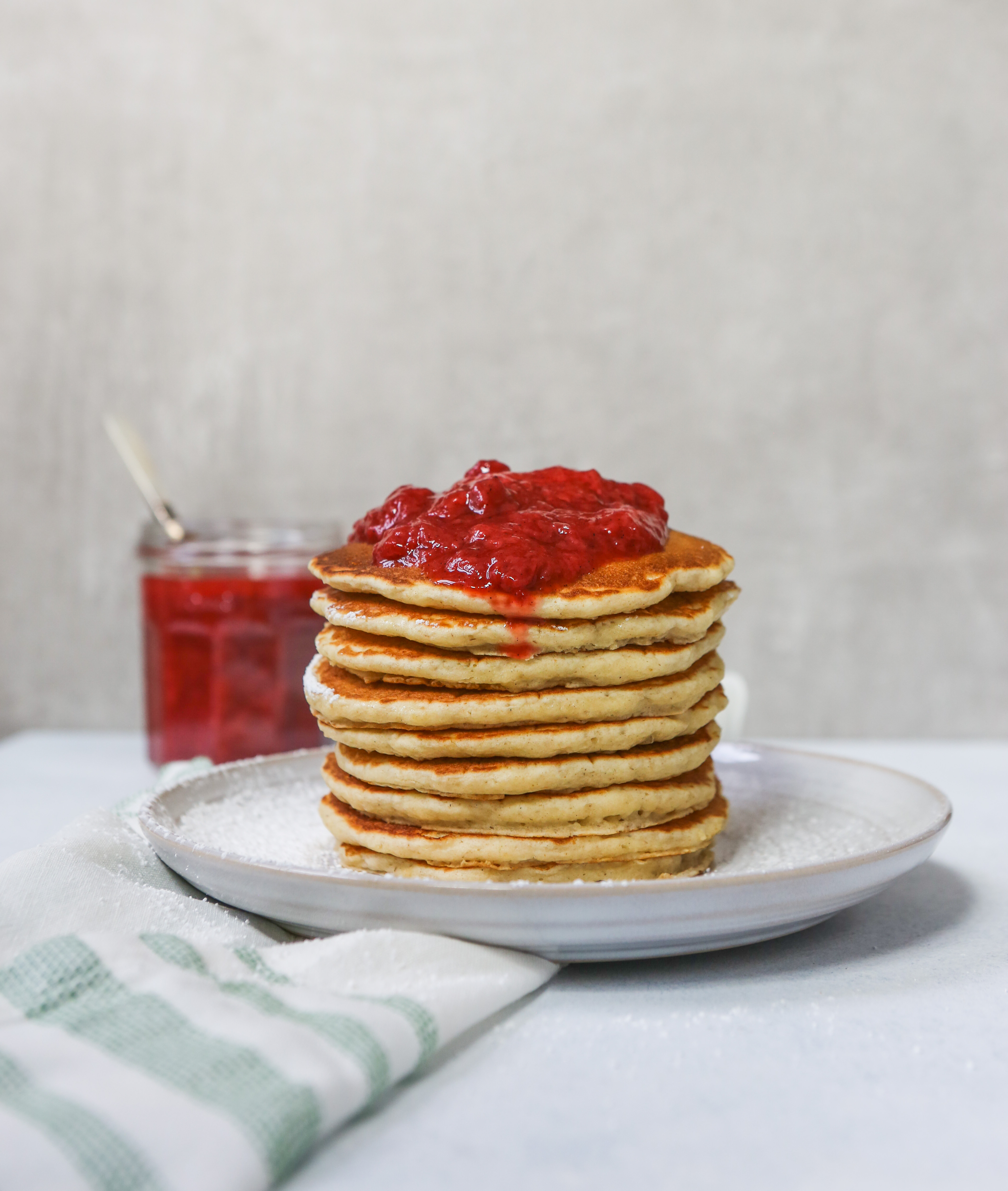 Toasted Oat Pancakes stacked on a white plate topped with a Quick Berry Compote