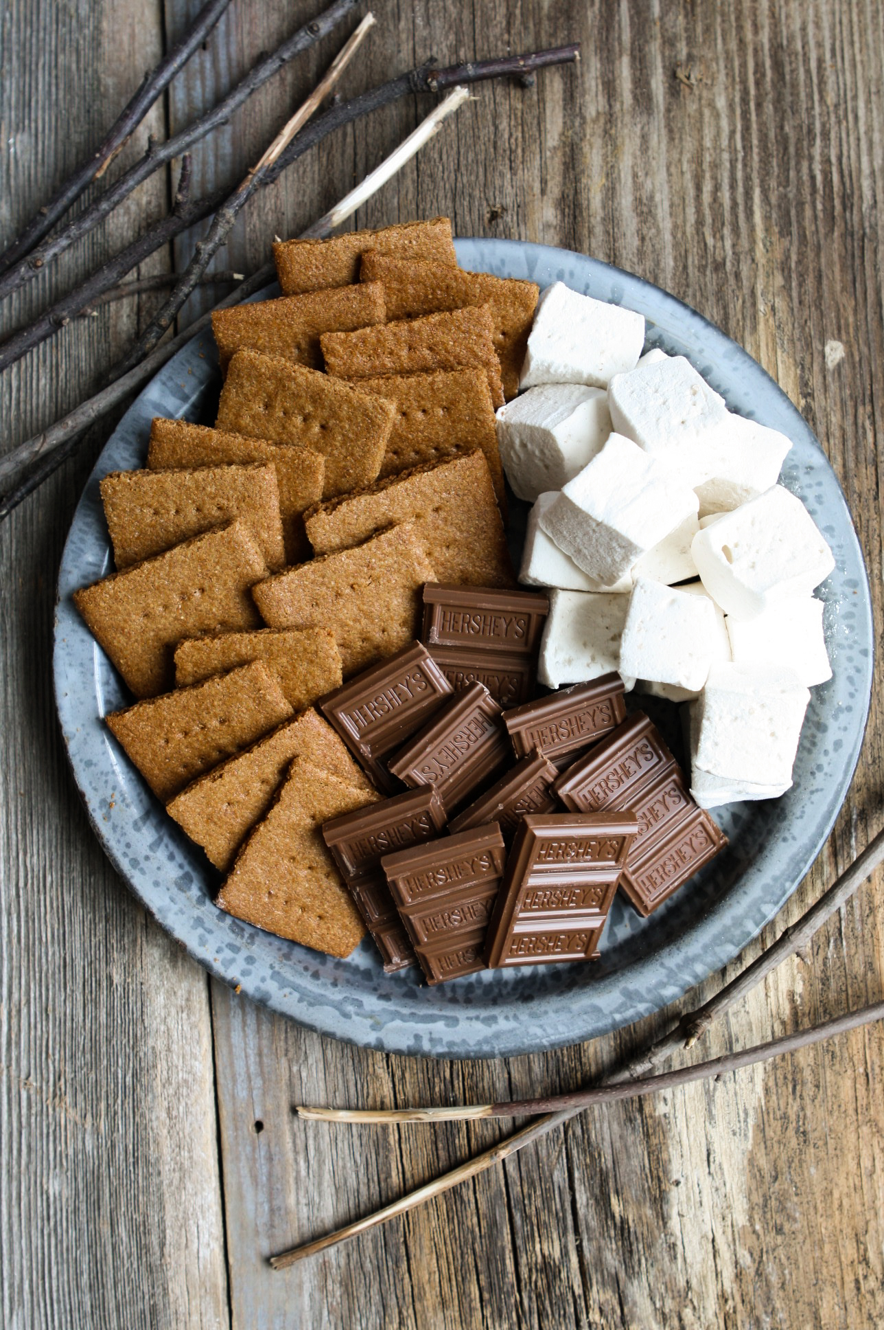 Homemade whole wheat graham crackers set on a metal camping plate with homemade marshmallows and chocolate bars.