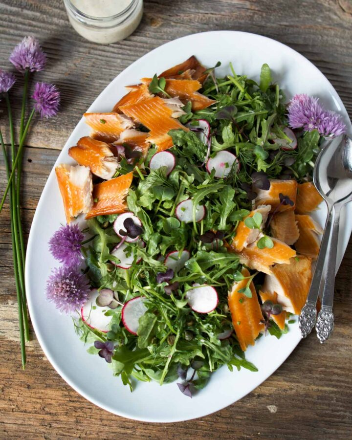 arugula, radishes and smoked trout on a white plate