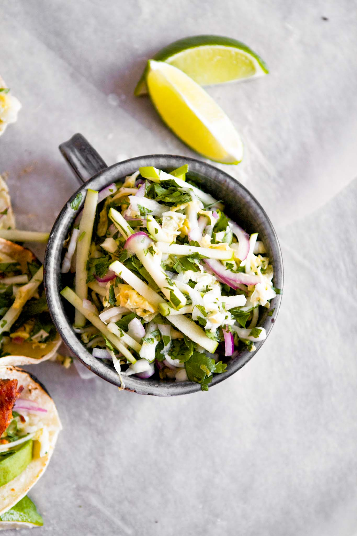 Overhead photo of green apple slaw in a small metal cup