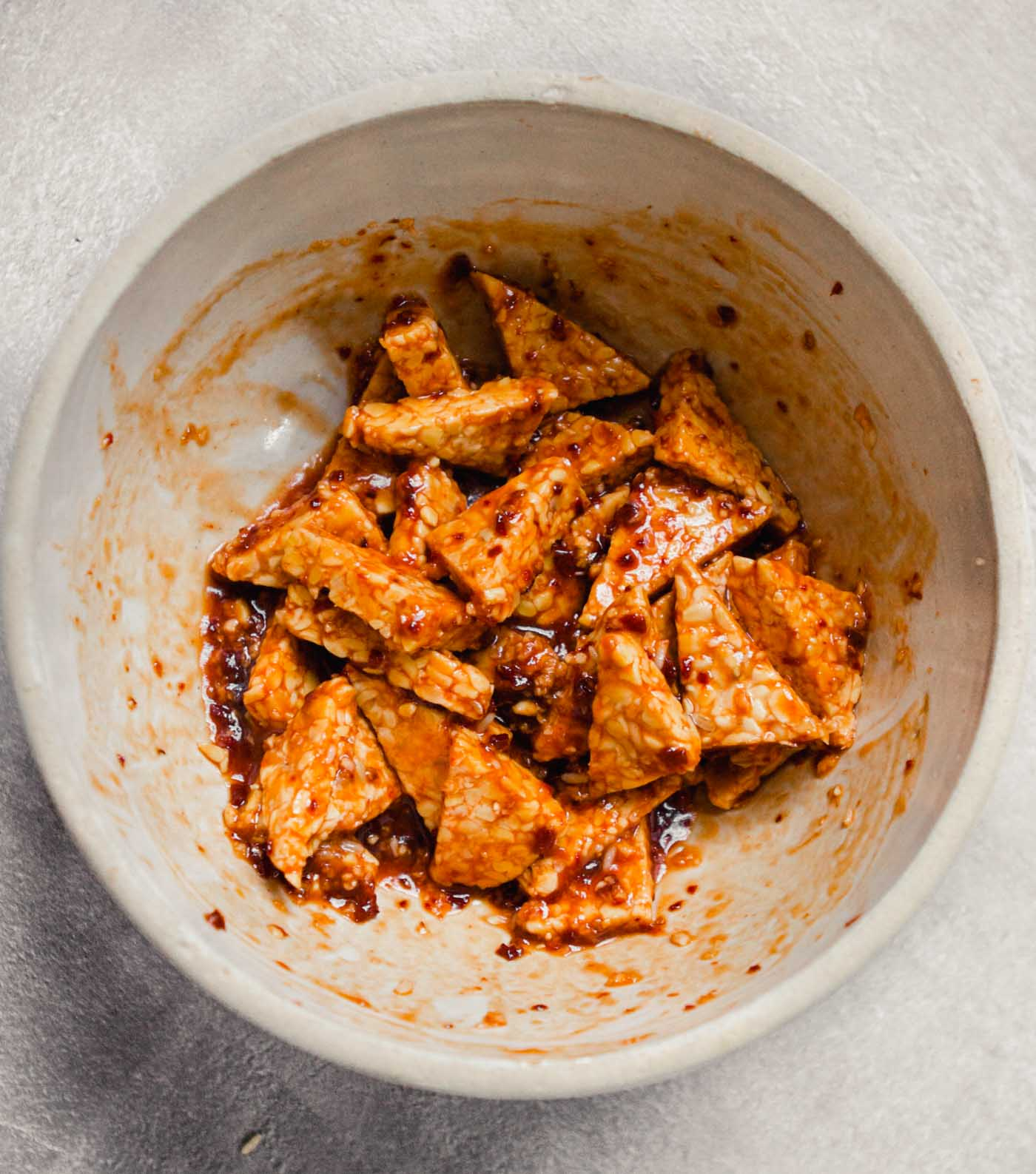 Photograph of tempeh marinated in a red sauce in a cream-colored bowl