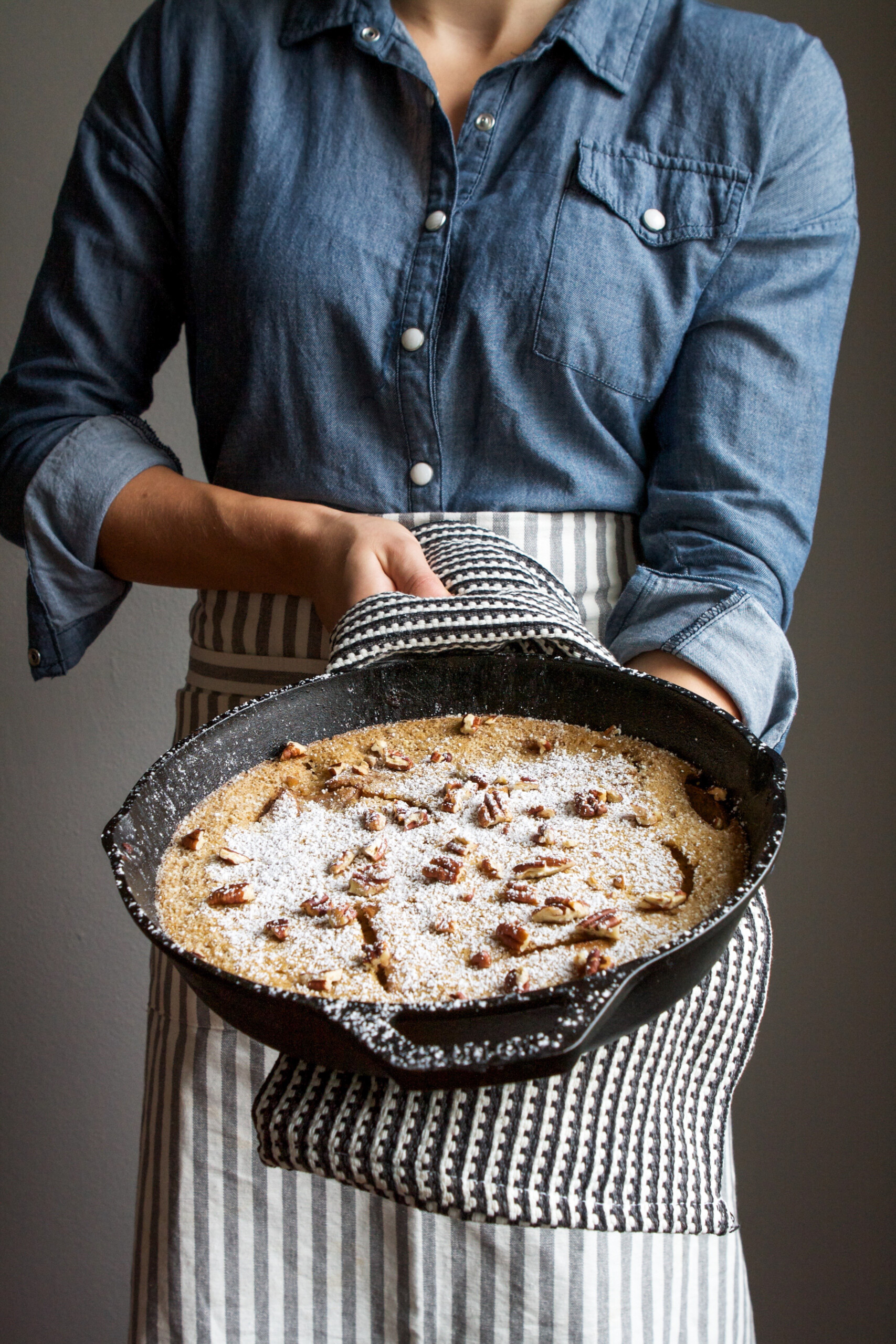 Photo of a cook holding a cast iron skillet with a puffed pancake in it