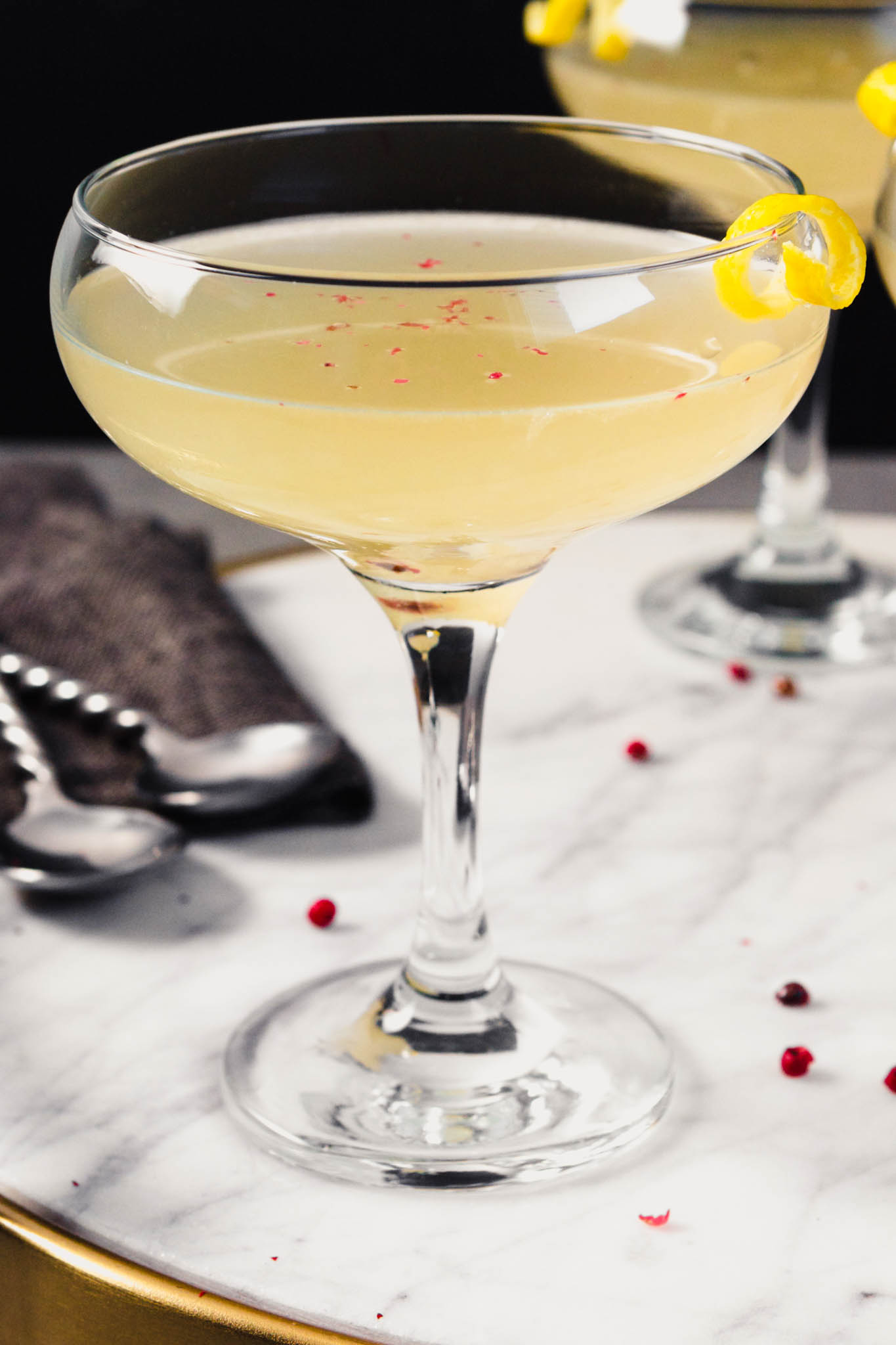 Photograph of a kombucha cocktail in a coupe glass on a marble platter