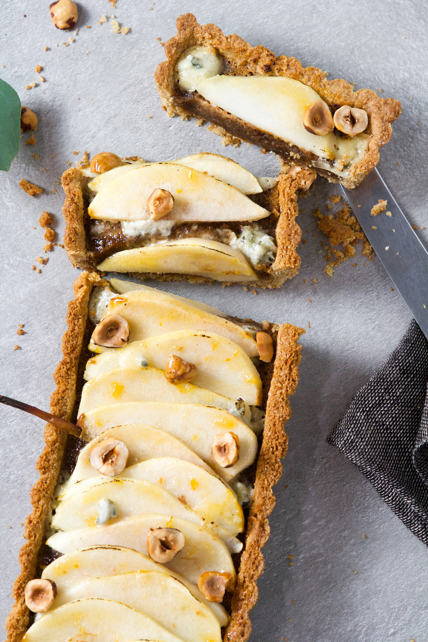 Photograph of a long pear tart on a gray background