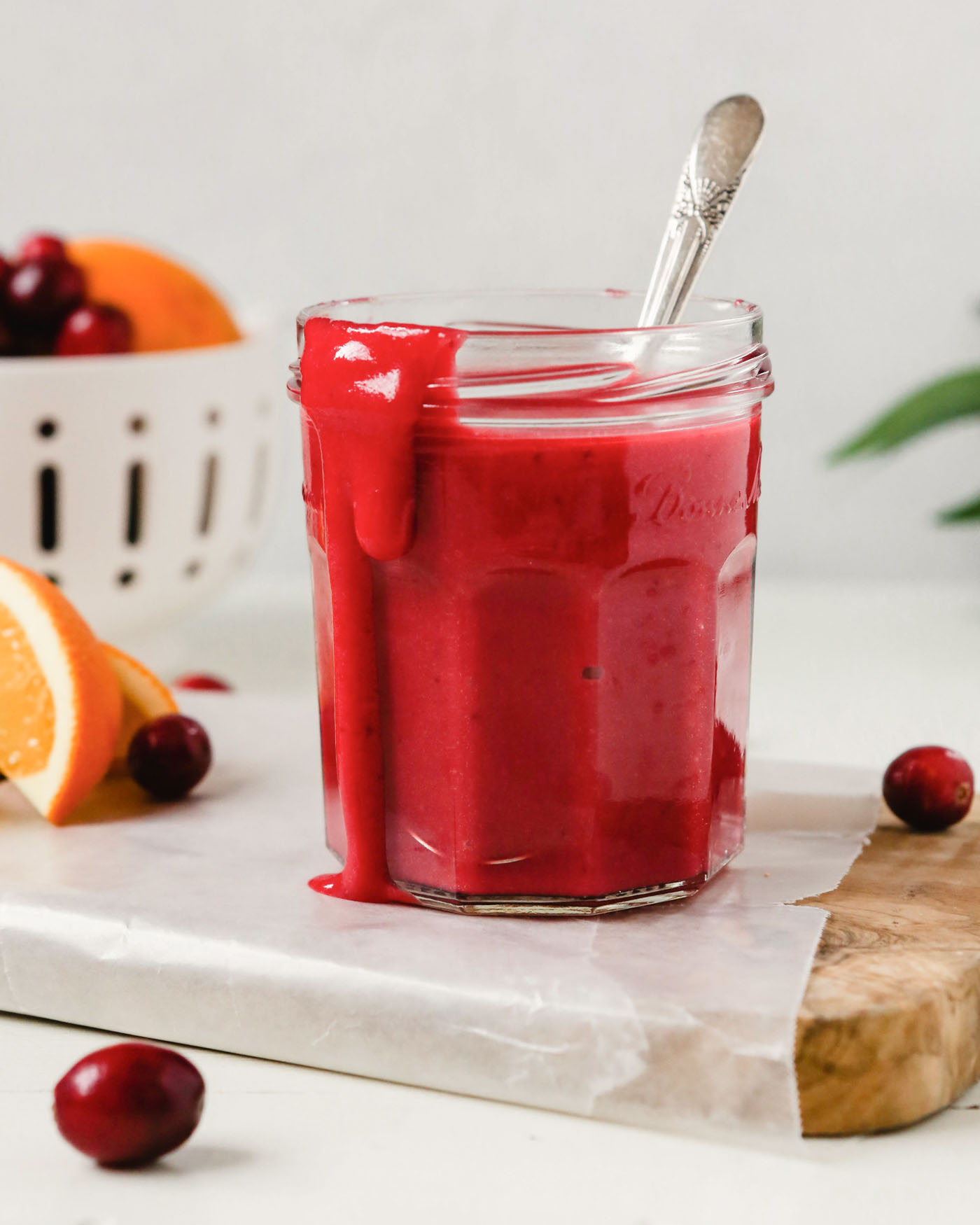 Side angle of a bright pink curd dripping out of a glass jar set on a wood cutting board