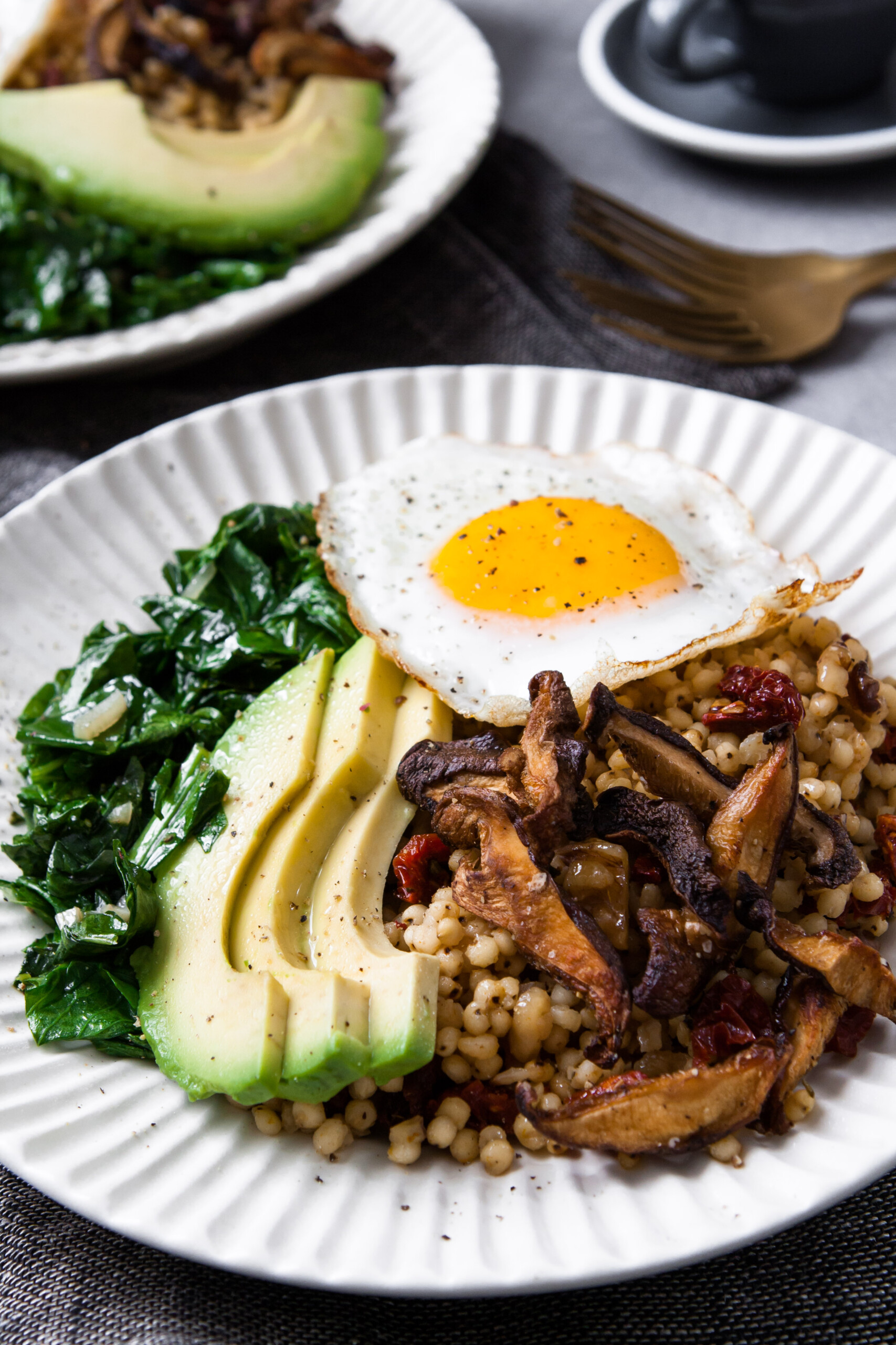 two white bowls filled with grains, sautéed greens, sliced avocado, and topped with a sunny side up egg