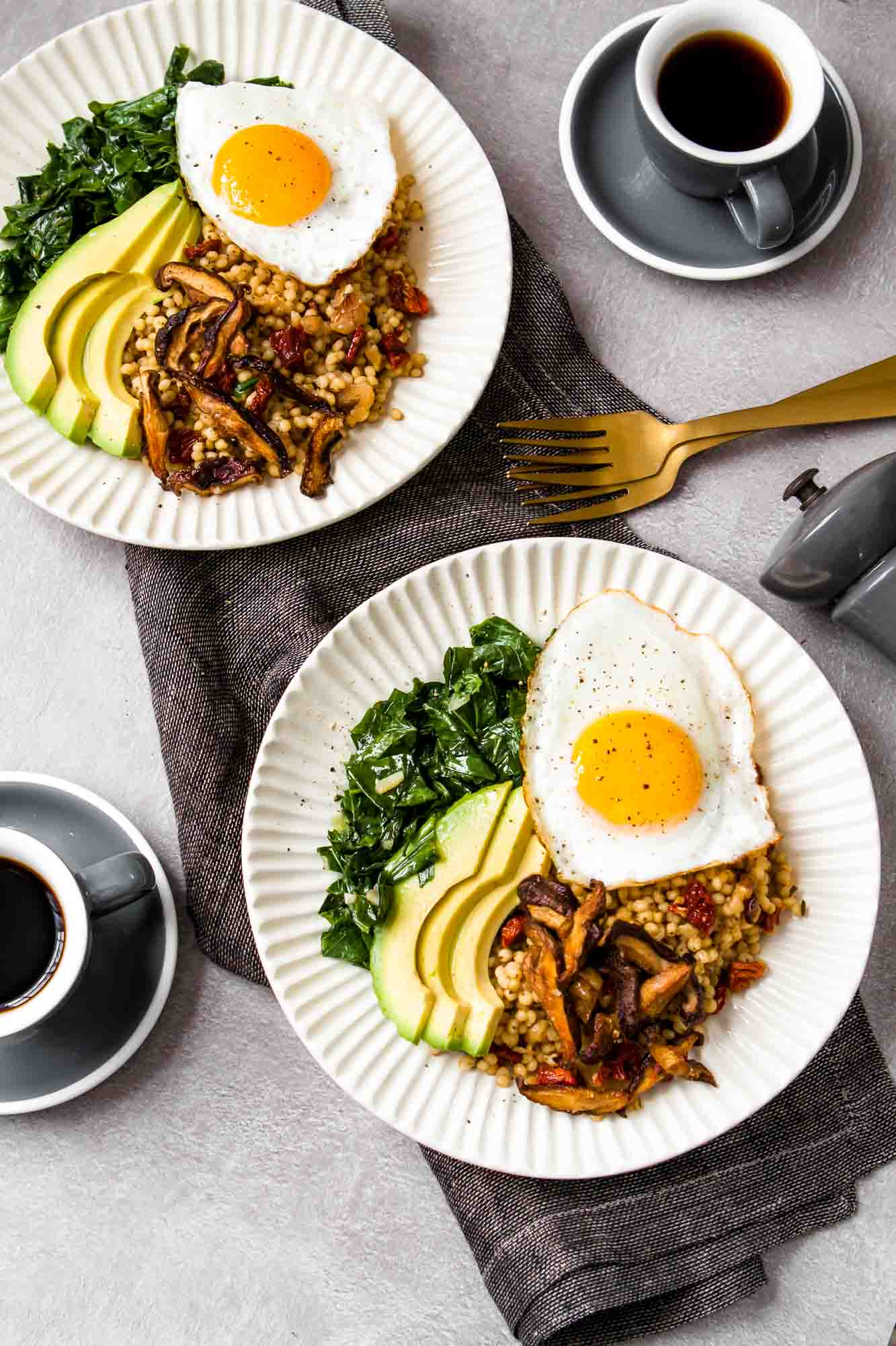 overhead image of cream-colored bowls piled high with sorghum, cooked greens, crispy mushrooms, an egg and avocado