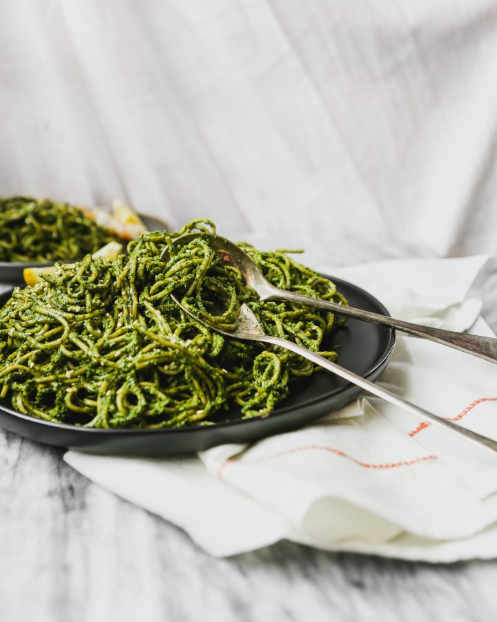 black plate with green pesto-covered pasta on top of marble with tarnished spoon