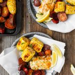 Roasted fish, potatoes, sausage, and corn on paper-lined metal plates set on worn wood surface.