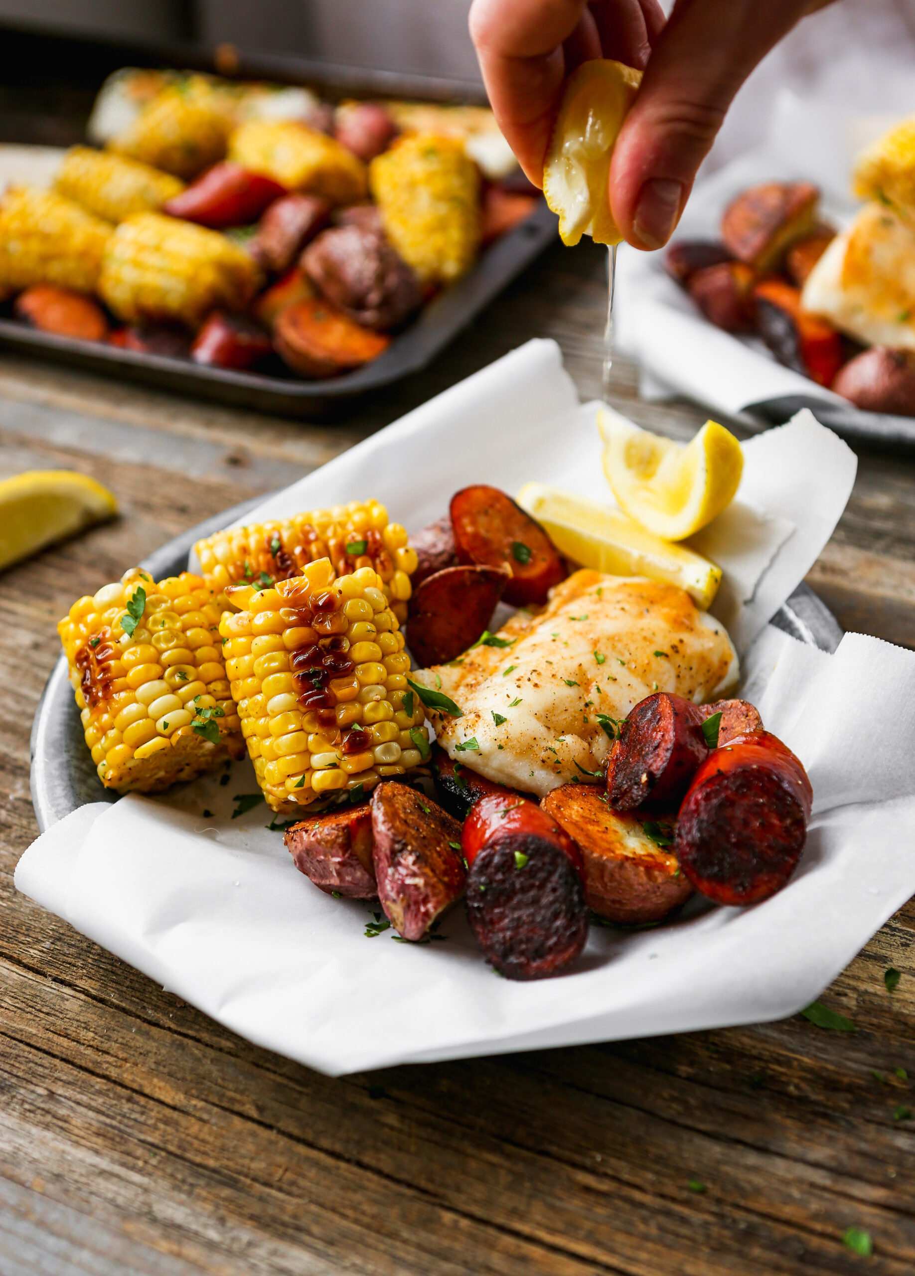 Lemon being squeezed over roasted fish, potatoes, sausage, and corn on paper-lined metal plates set on worn wood surface.