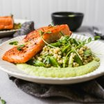 Seared salmon on white plates with green sauce and grain salad, set on a gray background.