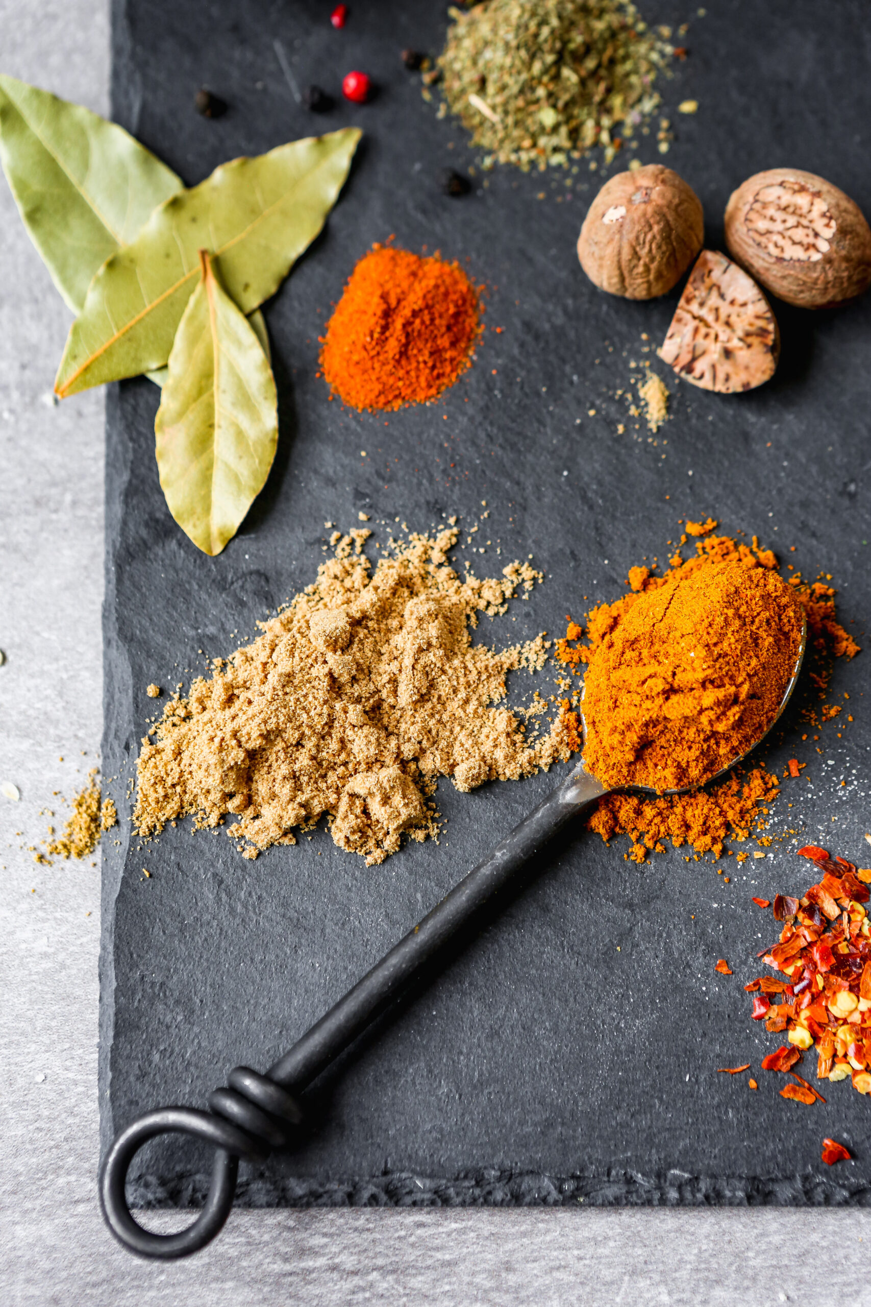 vibrant piles of colorful spices arranges on a black slate plate.