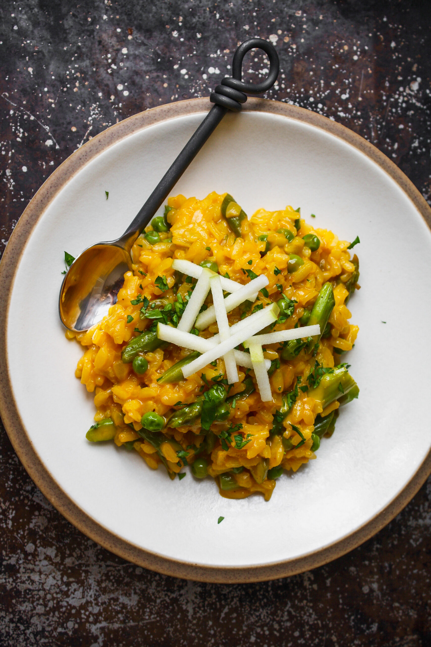 a white plate topped with carrot risotto, peas, and asparagus set on a worn metal background.
