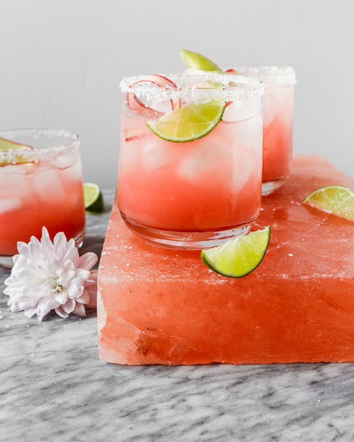 vibrant pink cocktail set on a pink salt block with lim wedges scattered around