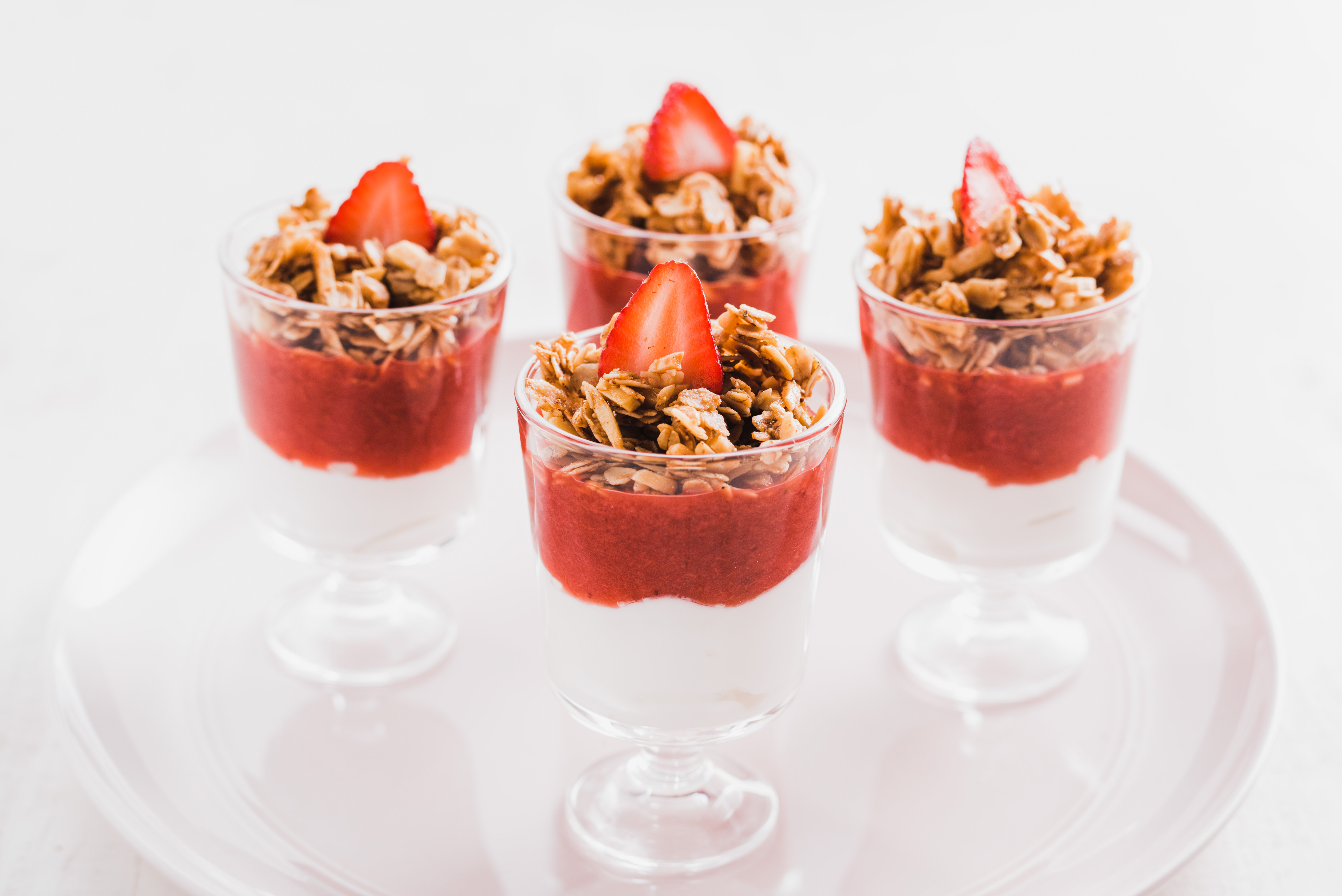 Yogurt and fruit parfaits with granola and strawberries set on a white plate