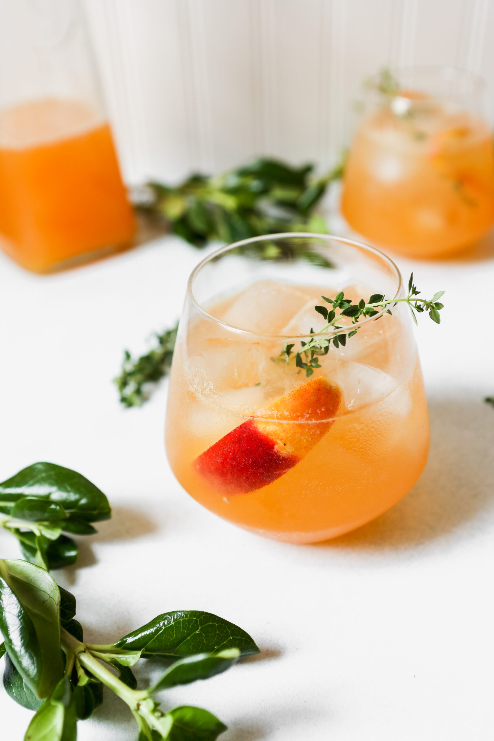 Peach and thyme cocktail photographed from overhead on a white surface. Fresh peach and thyme sprigs arranged around drink.
