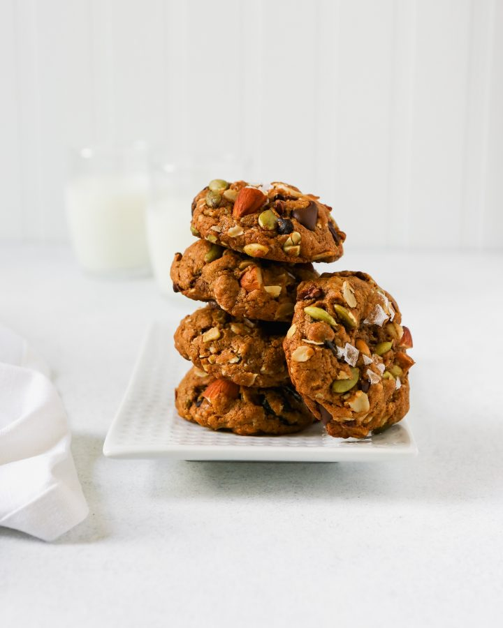 Chunky trail mix cookies stacked on a white plate on a white surface.