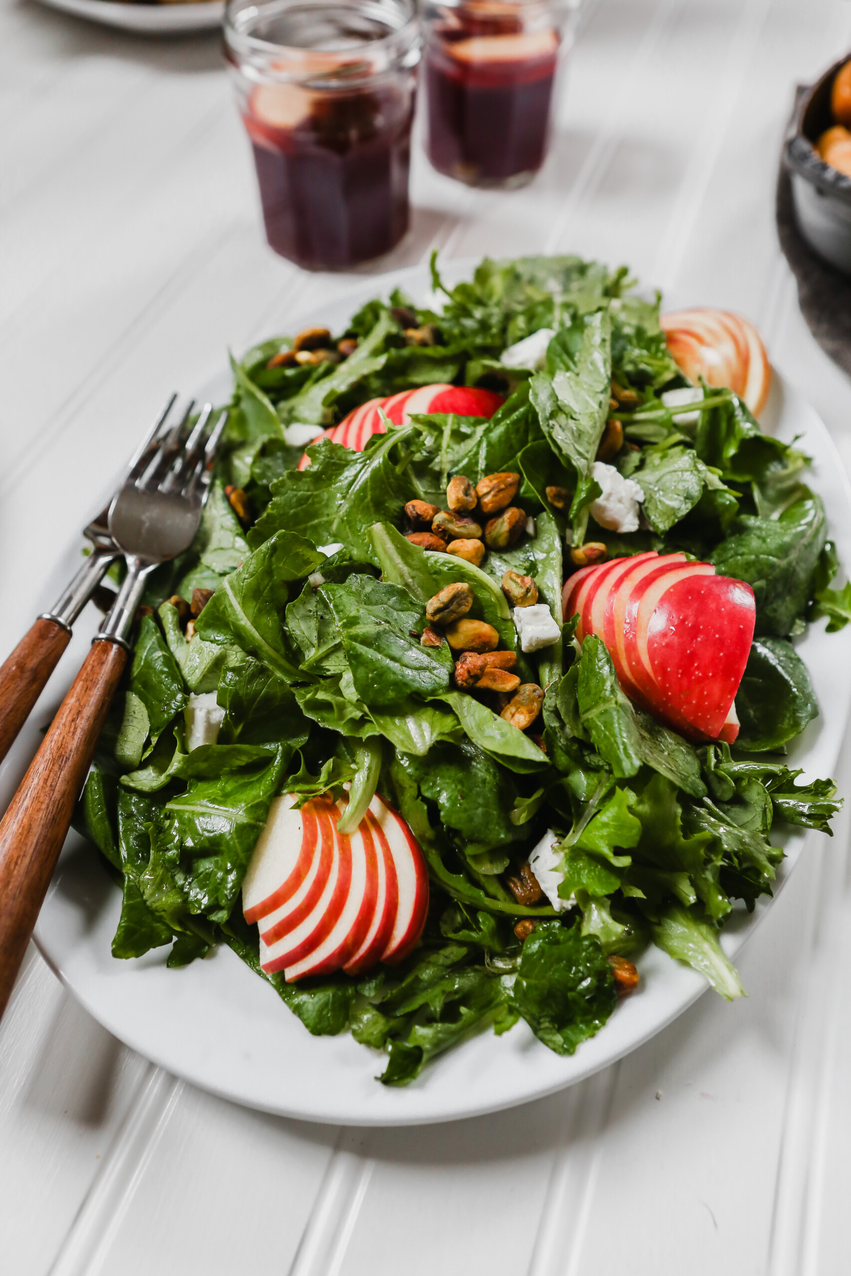 Photography of kale apple salad on a large white plate set on a white surface.