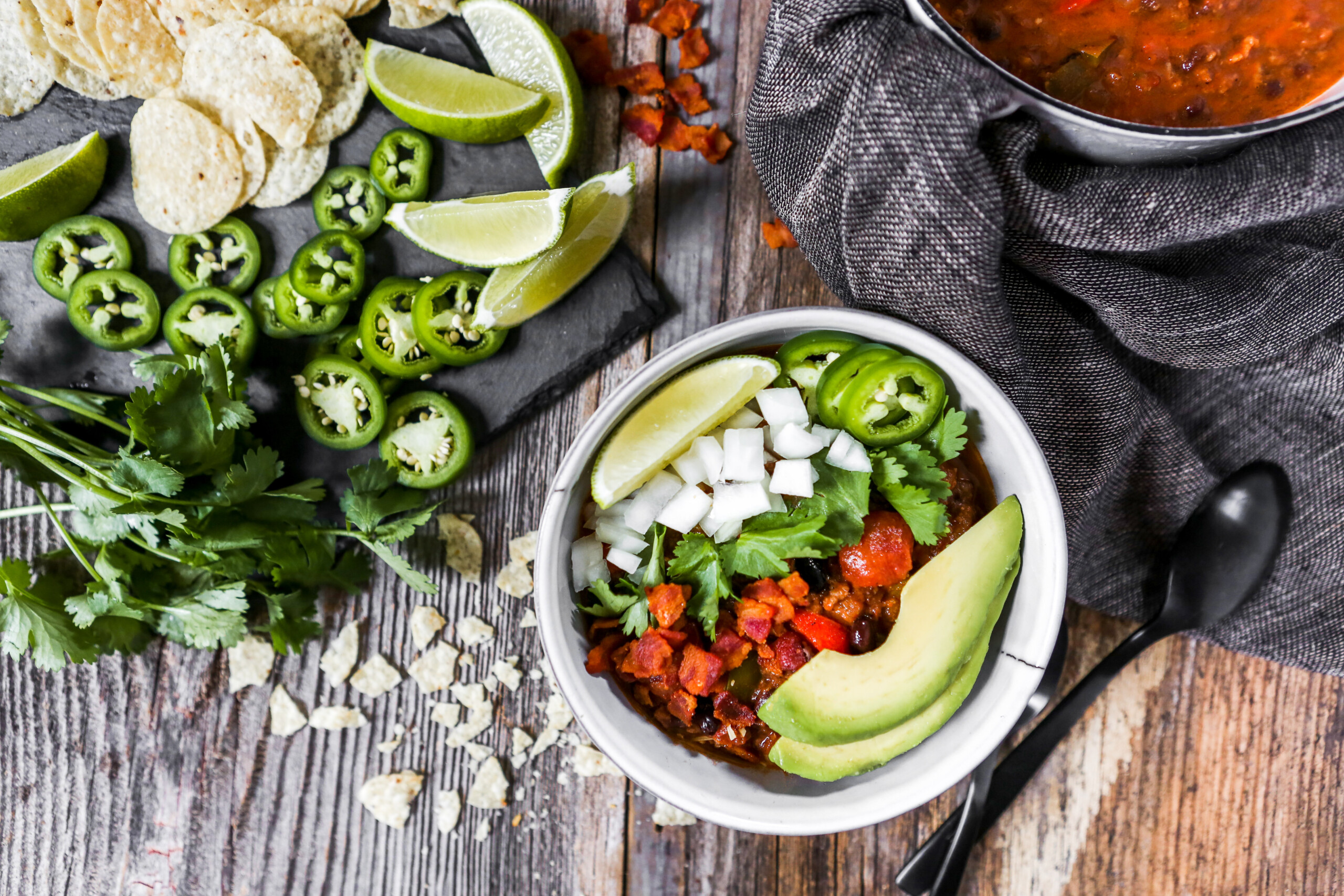 Photo of a bowl of chili topped with avocado, lime, onion, cilantro and jalapeno set on a wood table with chips