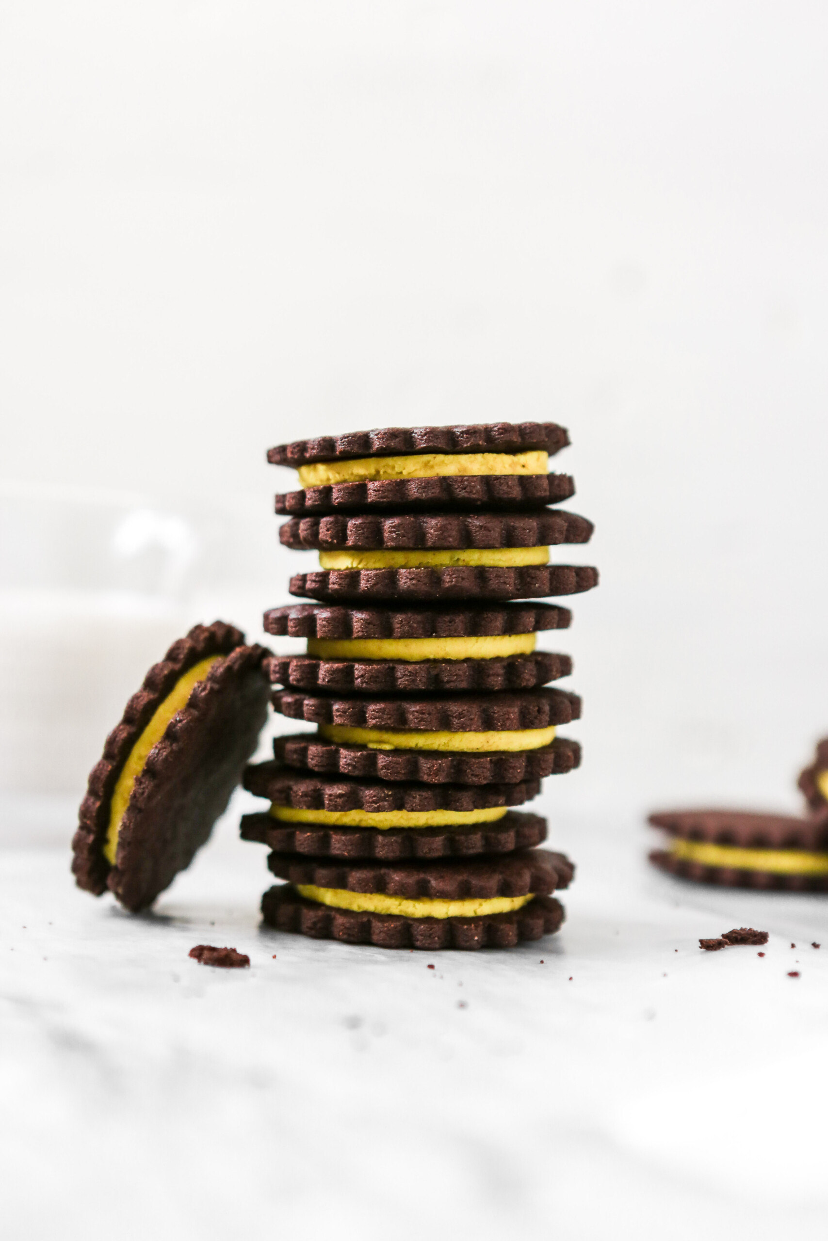 Photography of chocolate sandwich cookies with yellow frosting stacked on white marble.