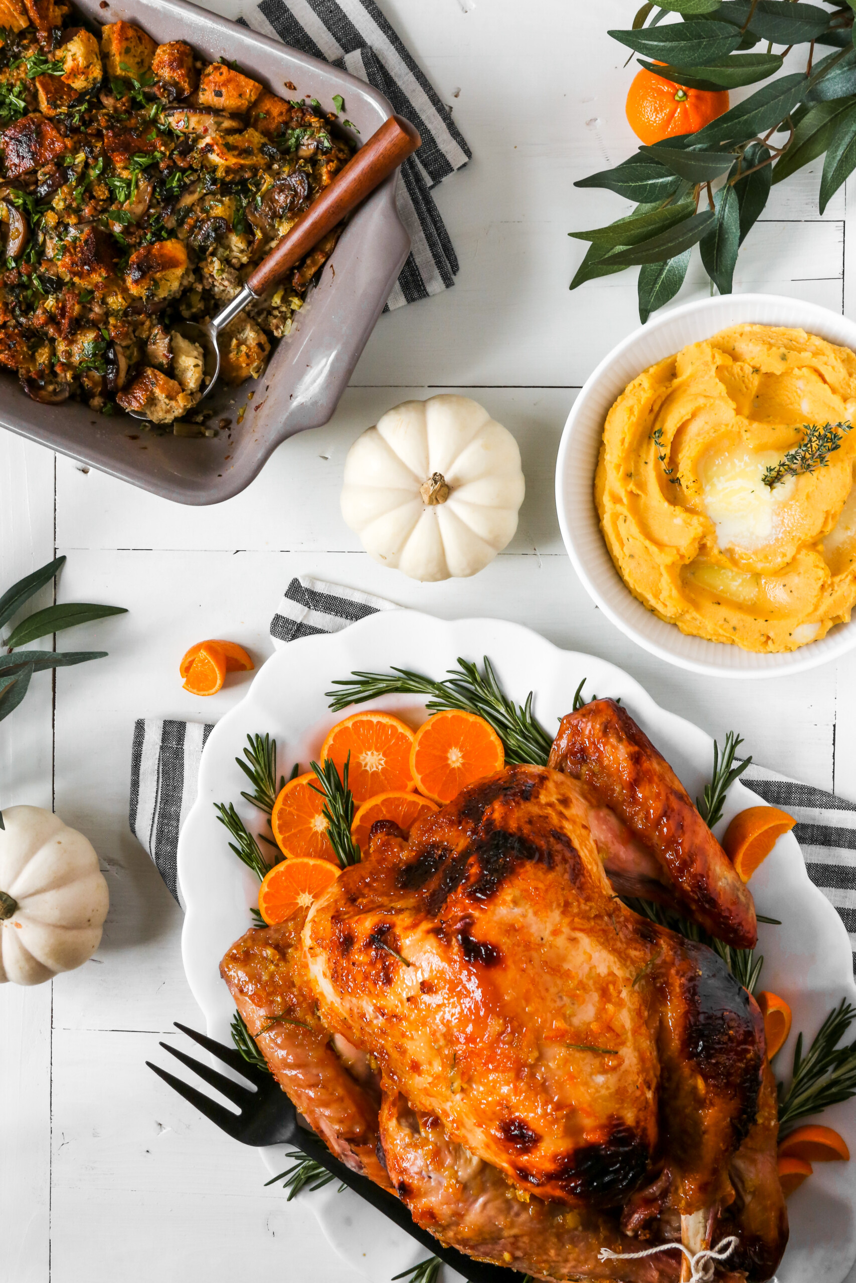 photograph of a Thanksgiving table scape and meal with a glazed roast turkey, stuffing, and mashed potatoes