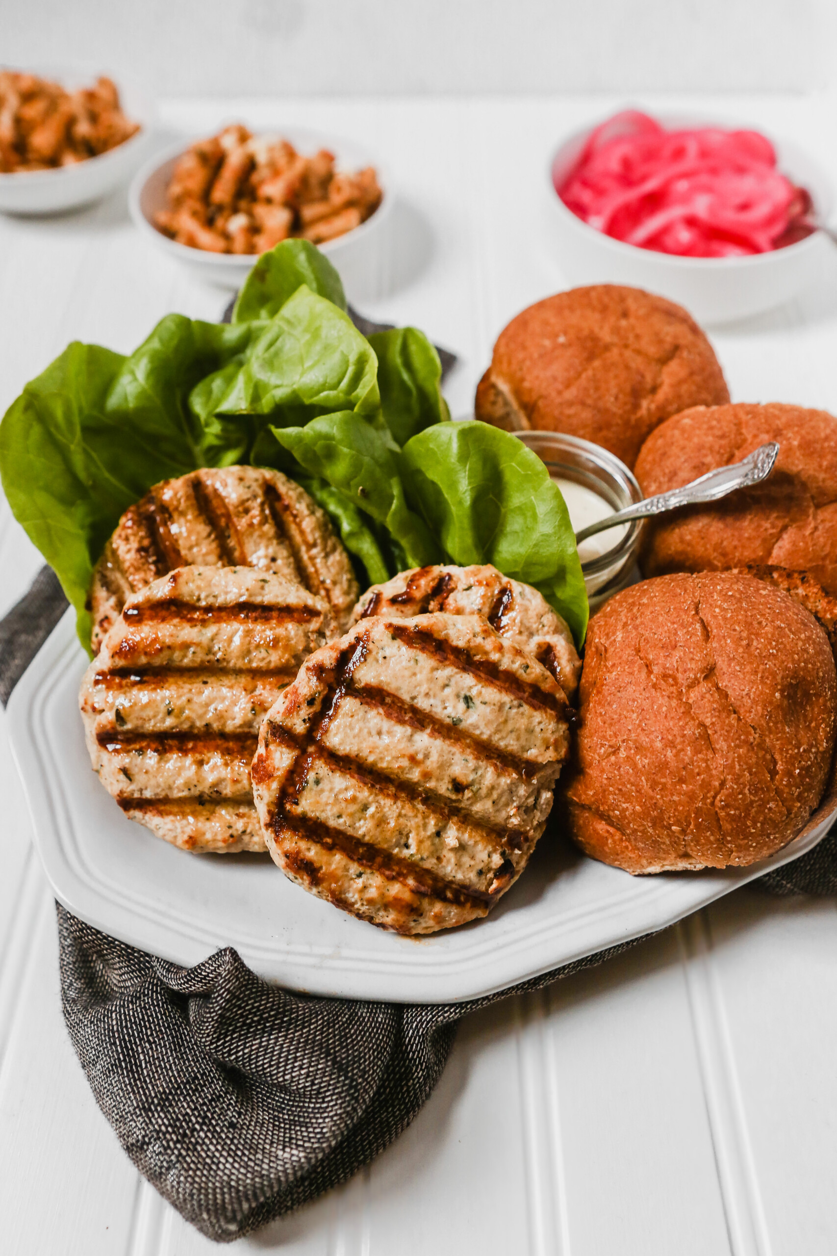 Photograph of turkey burgers on a large white platter with buns, lettuce, and yogurt sauce